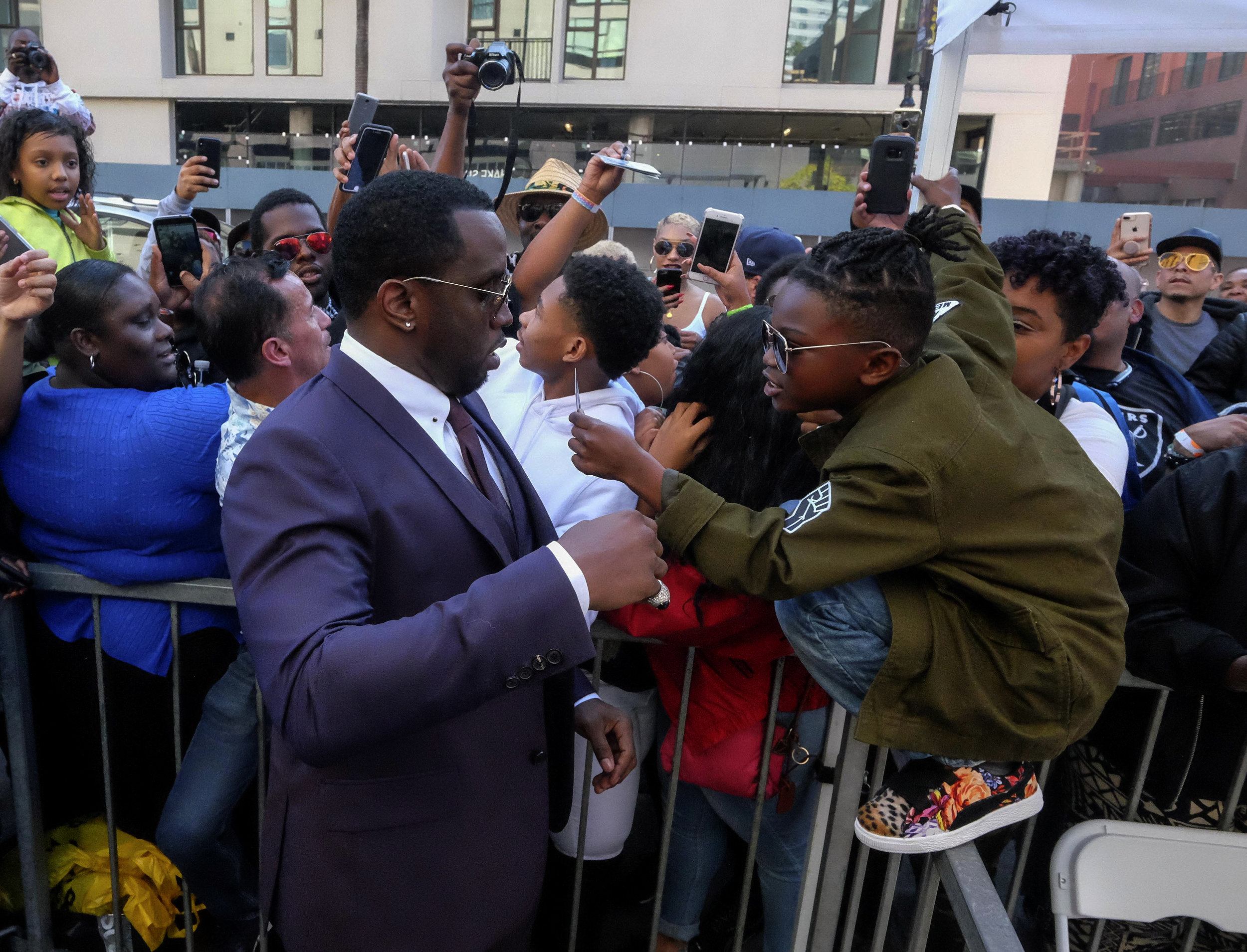 A young fan asks Sean 'Diddy' Combs for an autograph as he attends the ceremony honoring Mary J. Blige with a Star on The Hollywood Walk of Fame held on January 11, 2018 in Hollywood, California.