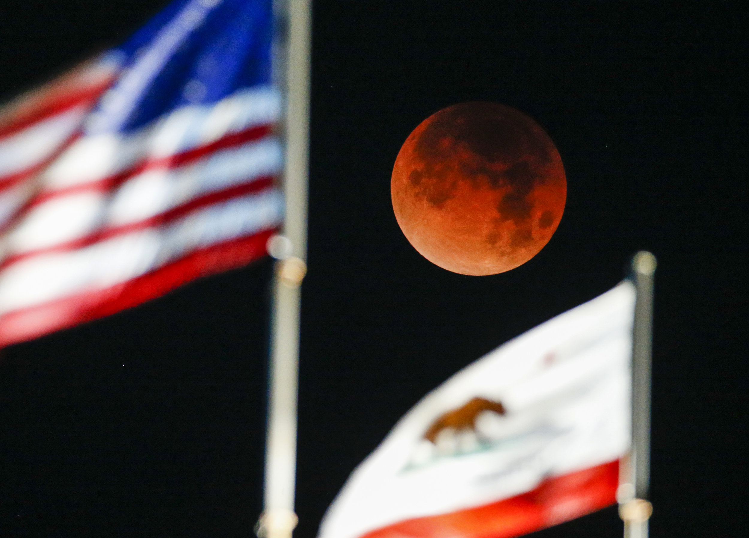 A rare celestial occurrence called a 'Super Blue Blood Moon' is seen behind the flags of U.S. and California State at Santa Monica Beach in Santa Monica, California, Wednesday, Jan. 31, 2018.