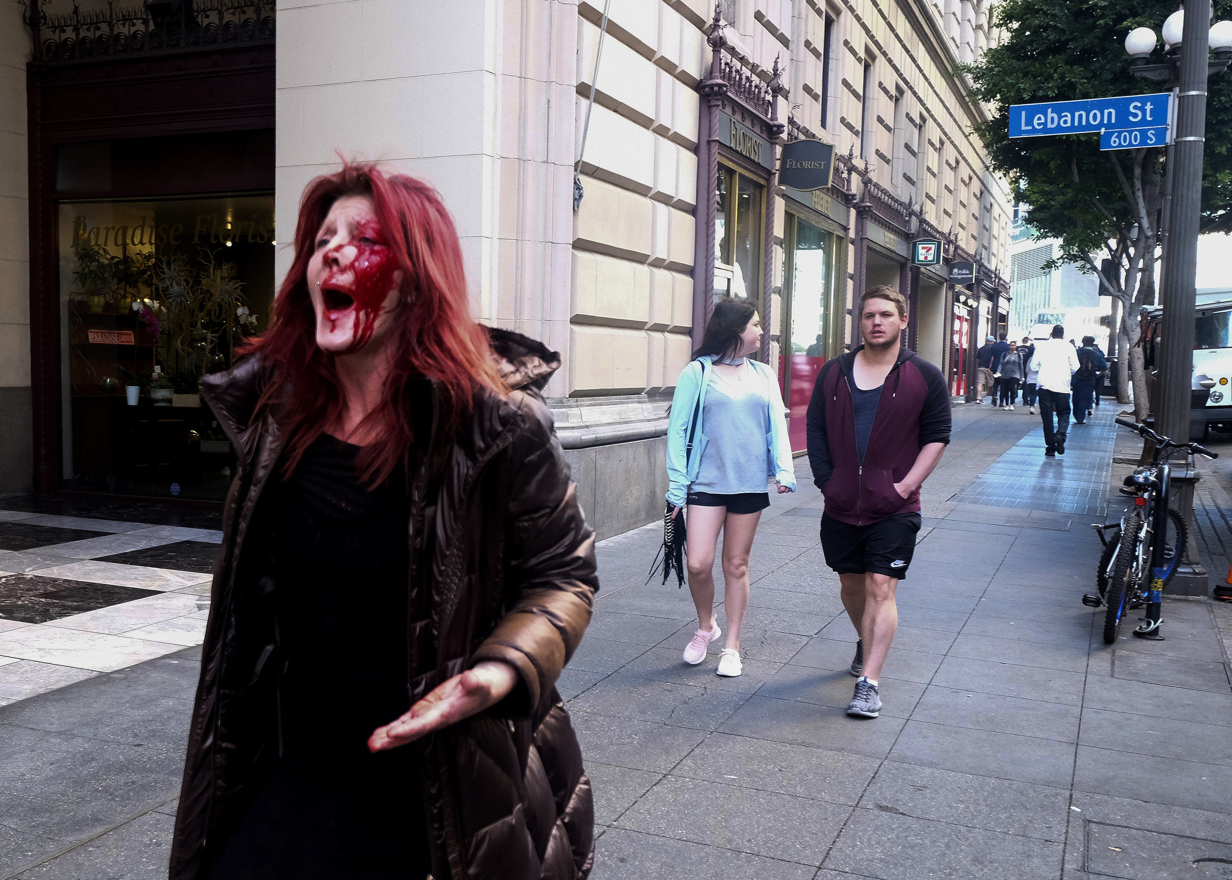 A woman with her face covered in blood after being assaulted by a man (white top in the back) in downtown Los Angeles, Wednesday, Jan 24, 2018. The suspect was taken into custody and it is believed he and the victim knew each other so this was not a random attack, police say.
