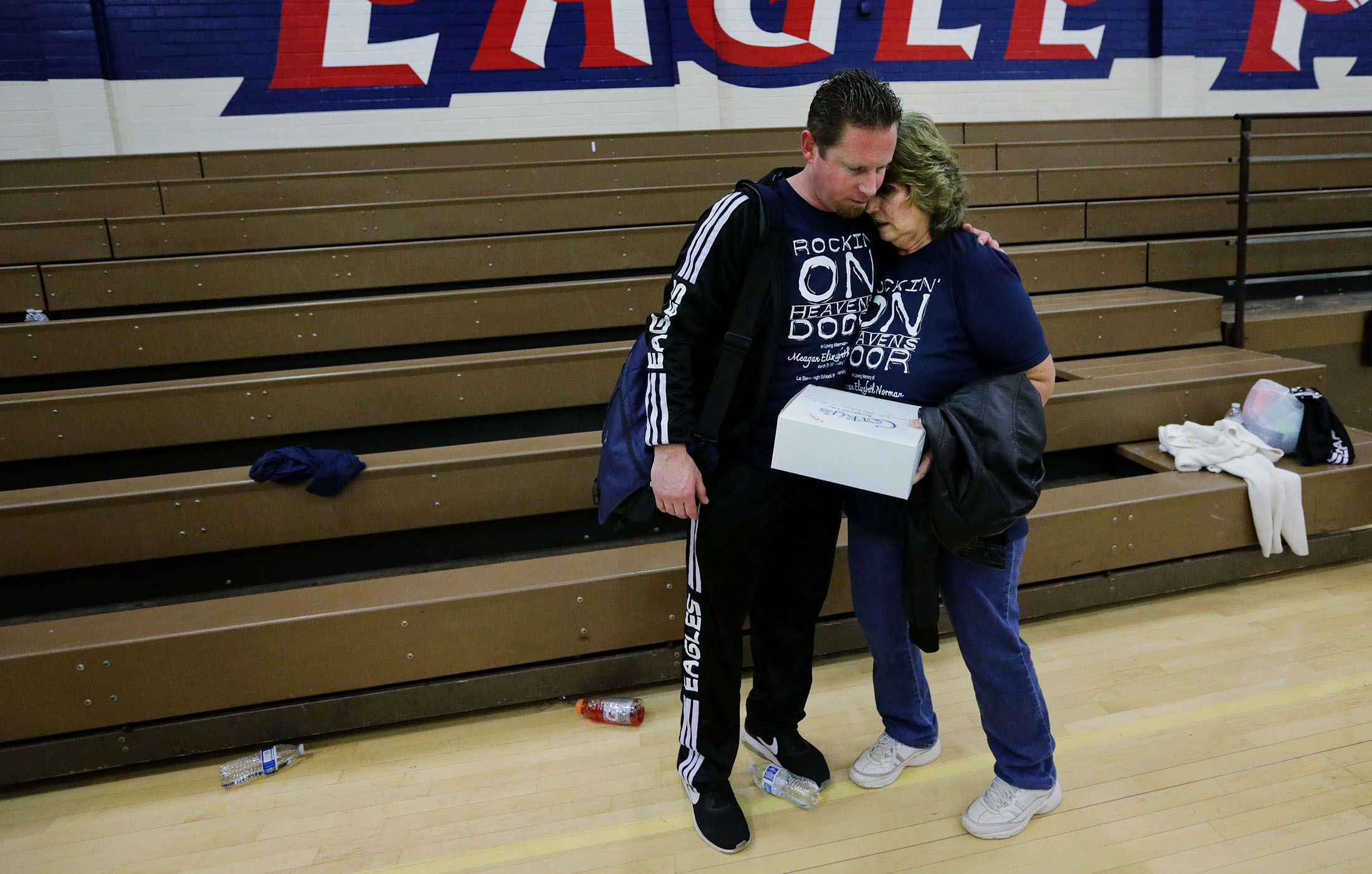 A family hug for La Sierra boys basketball coach Justin Norman and mother in law Claudia Duffield, 10 days after the sudden death of his wife and her daughter, Meagan. Norman was back on the court coaching La Sierra against the Patriots with the help and support of his family and friends in Riverside on Friday, January 11, 2019.