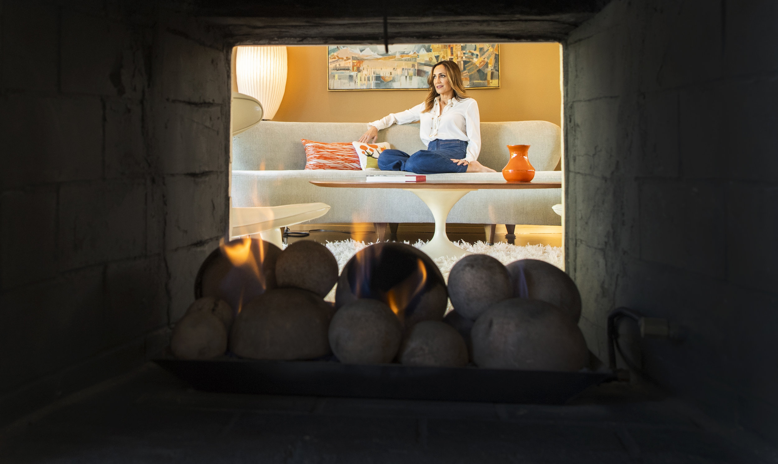 Rochelle Kramer is seen through the fireplace which heats both sides of the living room at her Cliff May Rancho home In Long Beach January 9, 2019.