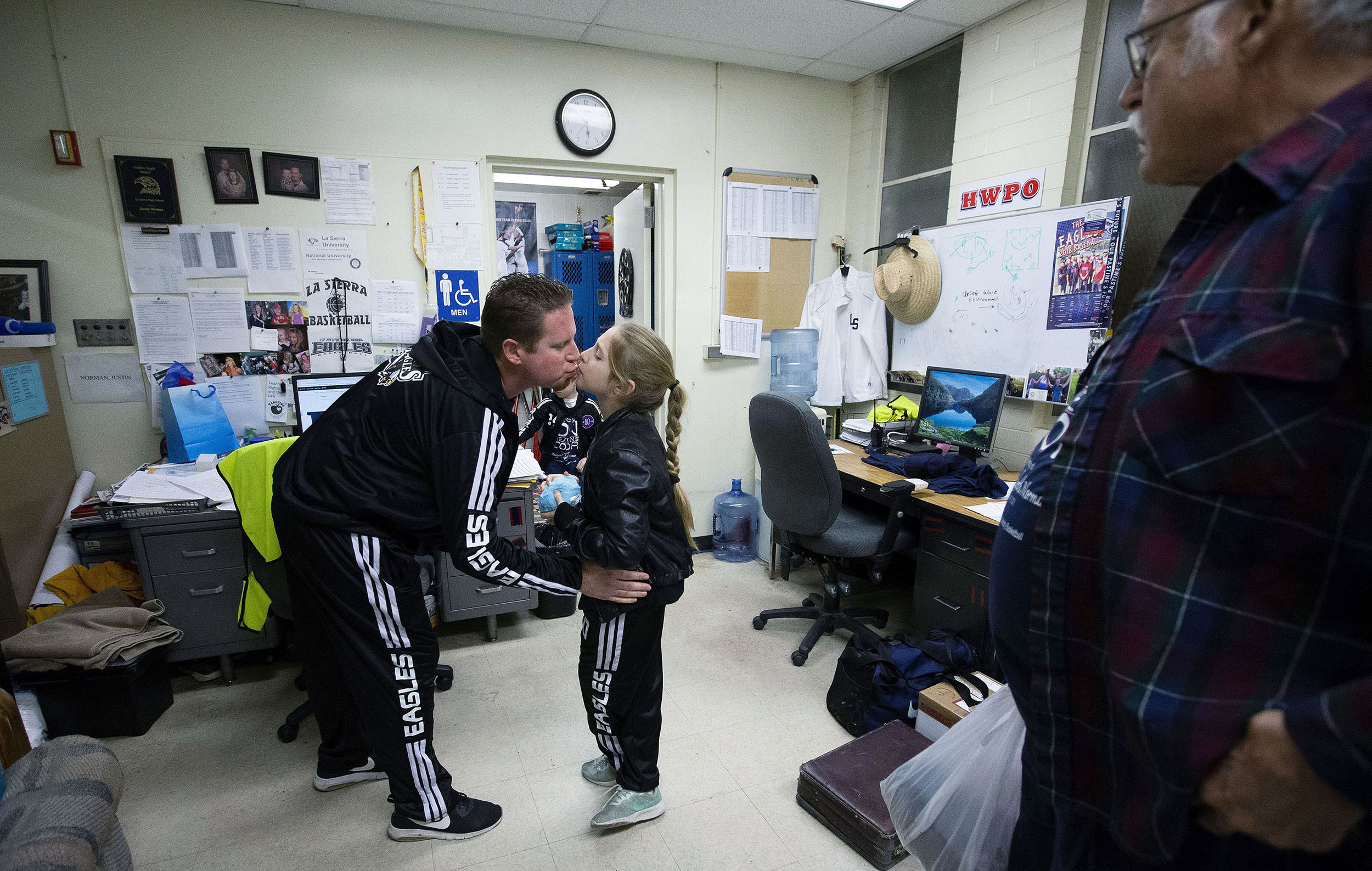 La Sierra boys basketball coach Justin Norman gets a kiss from his daughter Juliya Norman, 9, as grandfather Brian Duffield looks on in Norma's office before returning to the bench to coach the Eagles against Patriot 10 days after the sudden death of his wife, Meagan, at La Sierra High in Riverside on Friday, January 11, 2019.