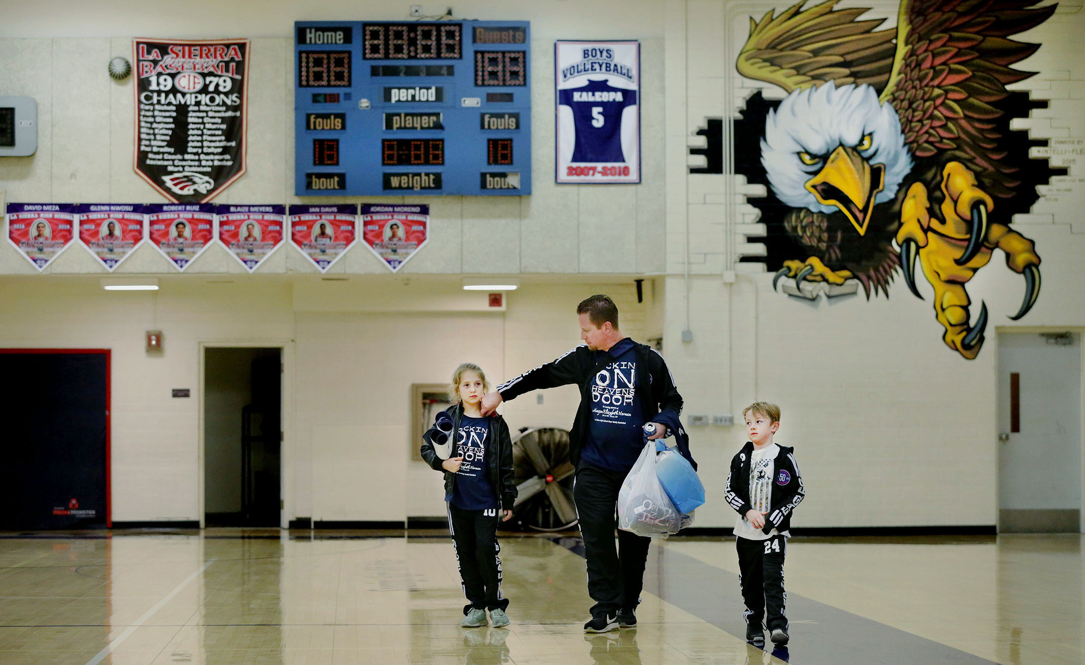 La Sierra boys basketball coach Justin Norman heads home with his children Juliya Norman, 9, left and Jake Norman, 5, after returning to the bench to coach the Eagles against Patriot 10 days after the sudden death of his wife, Meagan, with the help of family and friends in Riverside on Friday, January 11, 2019.