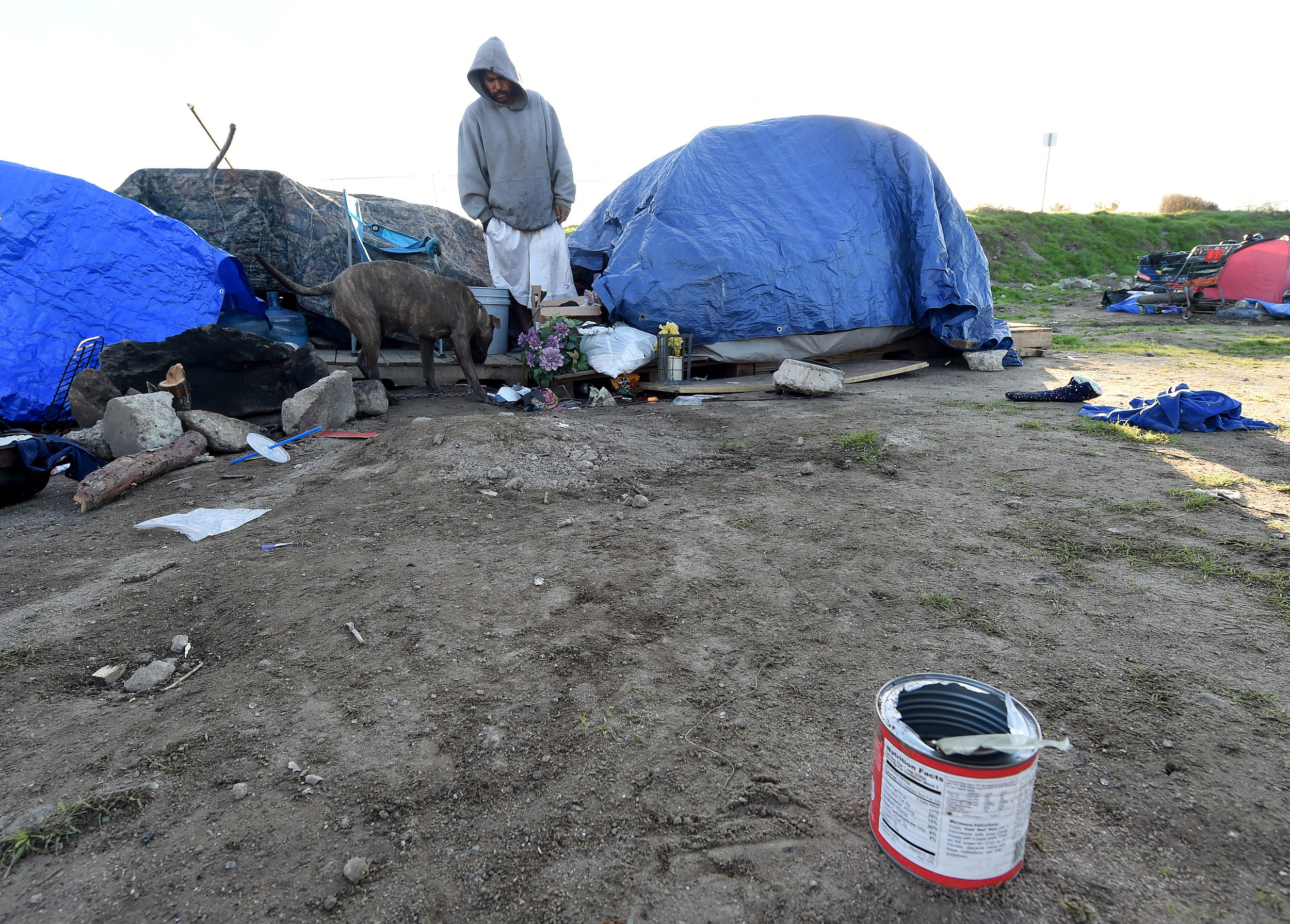 A homeless man stands outside his tent, along with his dog, in a homeless camp off of 9th Street in San Bernardino during the San Bernardino County 2019 Point-in-Time Homeless Count in downtown San Bernardino Thursday morning, January 24, 2019. The Point-in-Time Homeless Count (PITC) is a one-day street-based and service-based count and subpopulation survey of sheltered and unsheltered individuals to identify how many people in San Bernardino County are homeless and their subpopulation characteristics on a given day. Information was also given out to help those who wished to improve their situation.