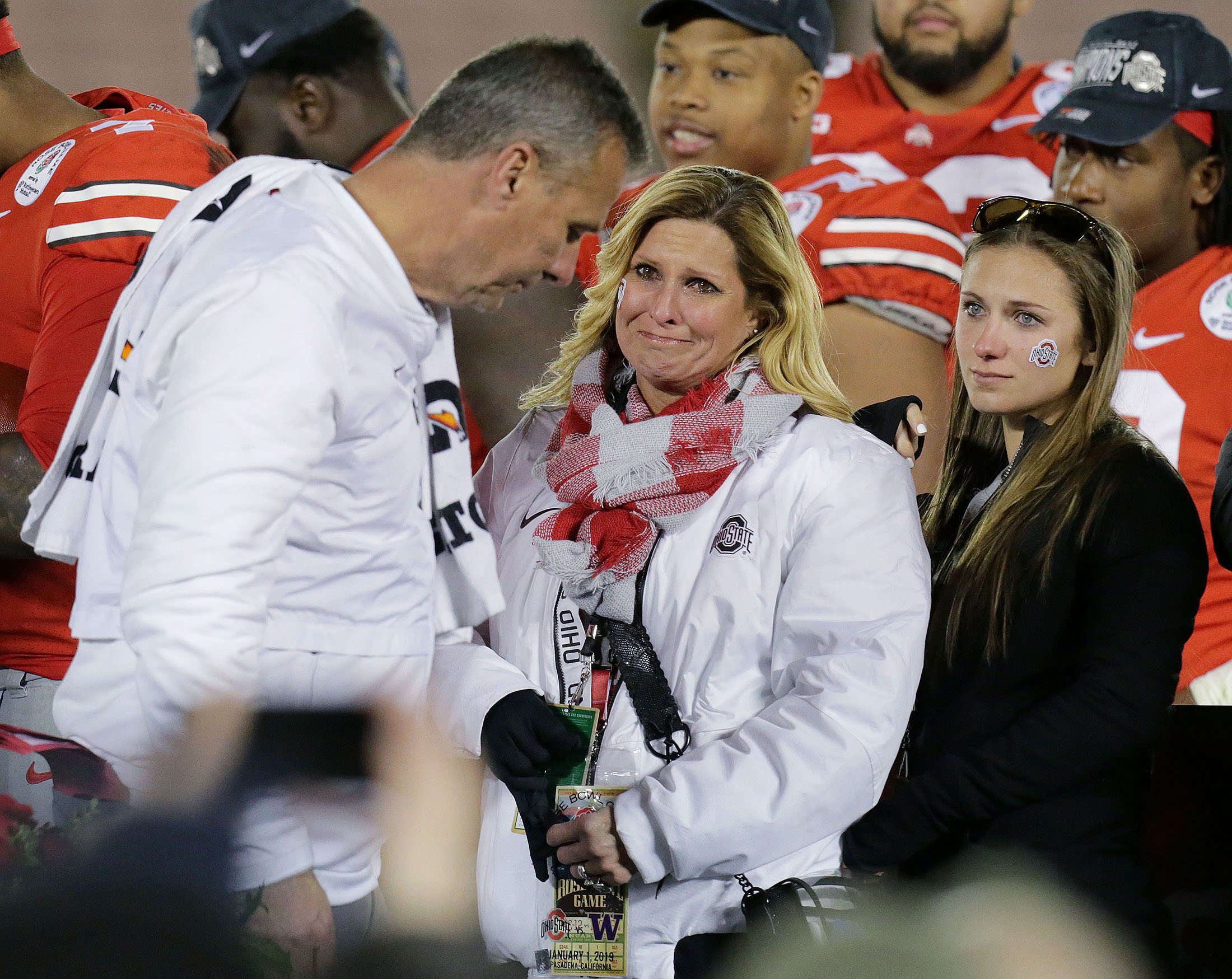 Ohio State Buckeyes head coach Urban Meyer lowers his head as he walks off stage after winning his last game as head coach at Ohio State while his wife, Shelley Mather Meyer and daughter cry as they watch him at the end of the 105th Rose Bowl game in Pasadena on Tuesday, January 1, 2019.