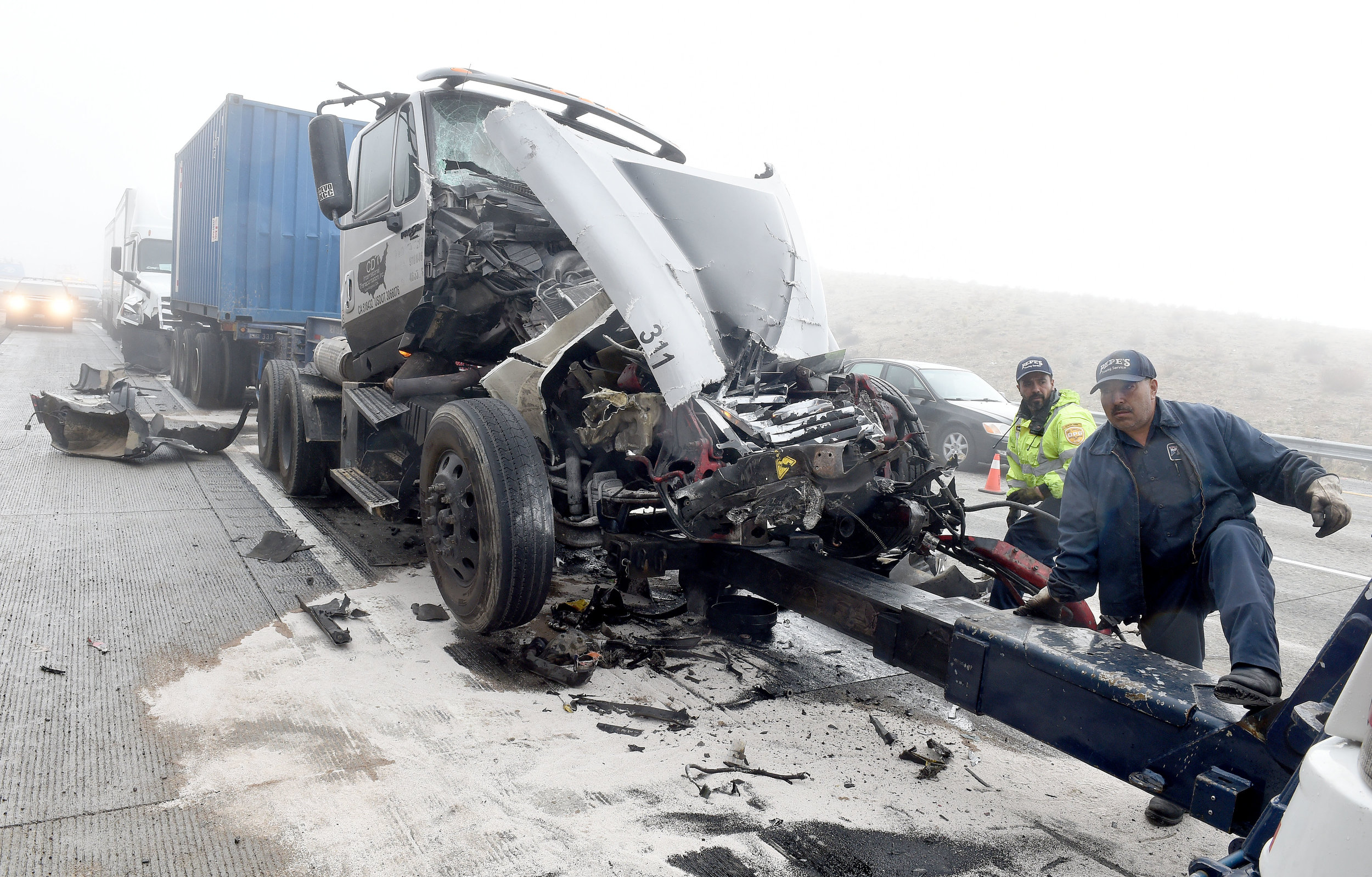 Crews work to clear one of the crashed big rig trucks involved in a major pile up on the southbound I-15 Freeway in the Cajon Pass Wednesday morning. The southbound I-15 Freeway was shut down in the Cajon Pass Wednesday, January 16, 2019 for several hours following a major pile up at approximately 9 a.m. involving at least 19 vehicles which was believed to be weather related. No major injuries were reported.