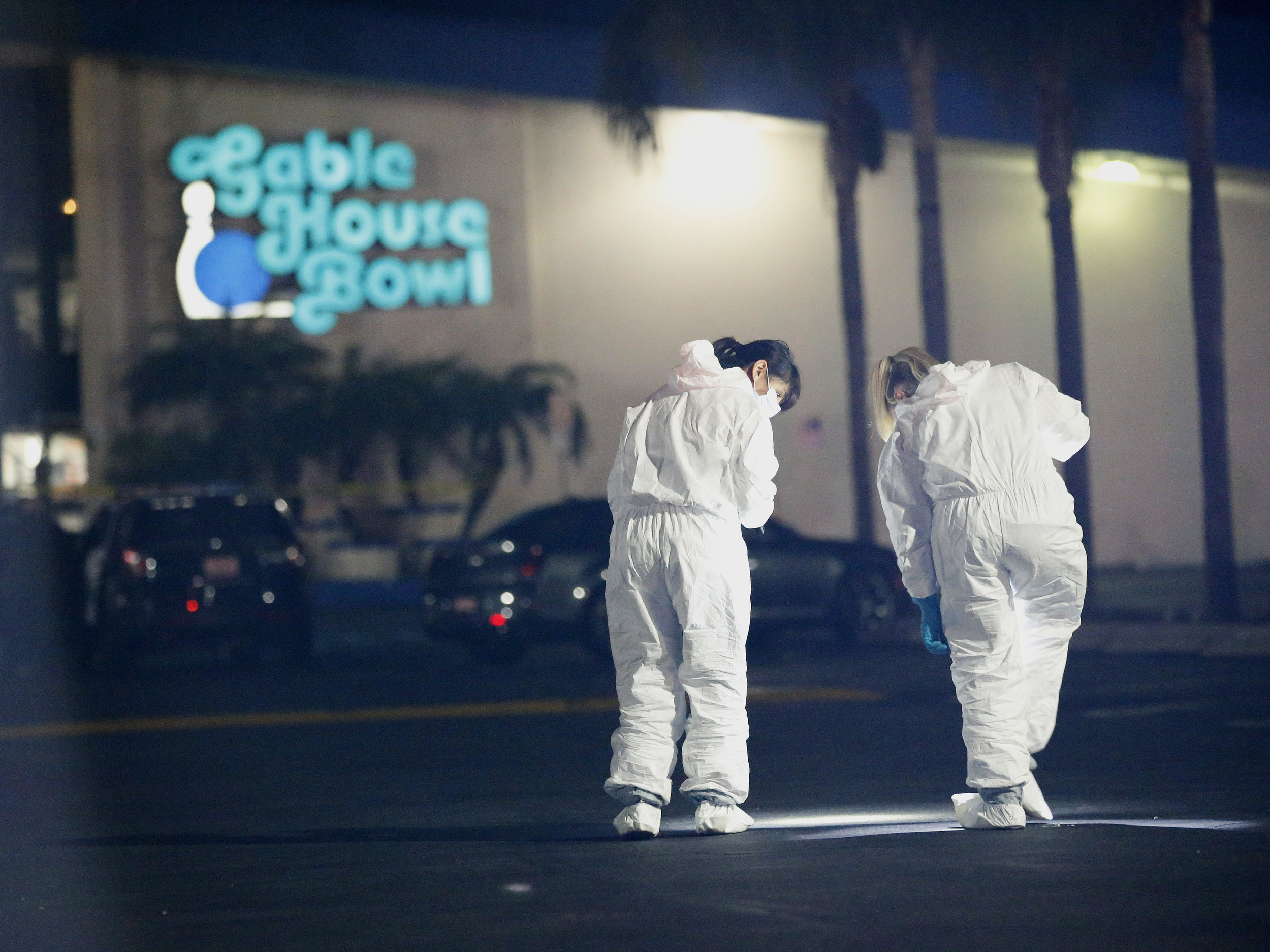 Police officers and investigators work the scene after a fatal shooting in Torrance, California, Saturday, Jan. 5, 2019. Three people died in a shooting at a bowling alley in Torrance and four others were injured, authorities said.