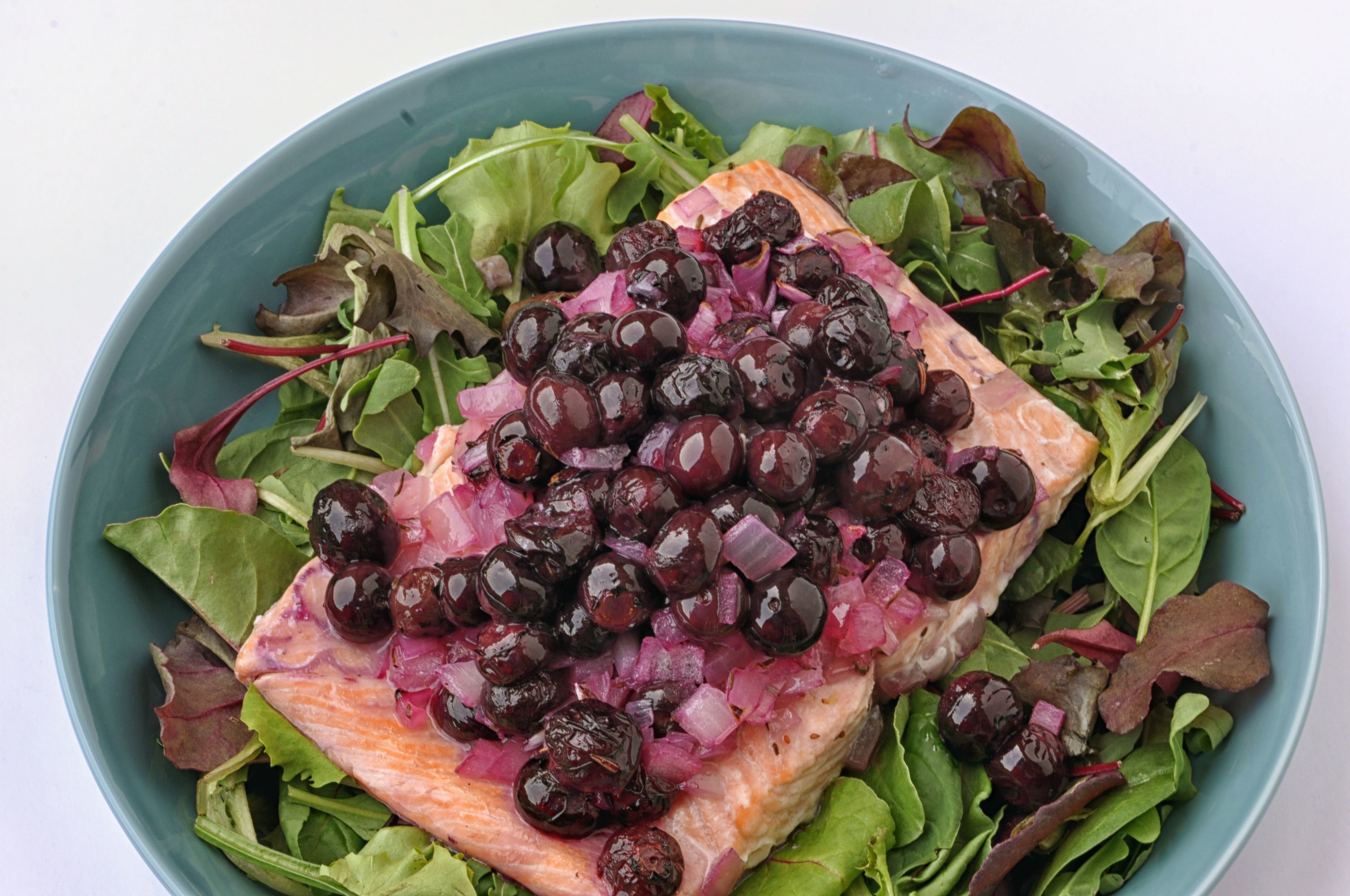 Salmon with blueberries and white wine on a bed of mixed greens. A healthy lunch or dinner recipe.