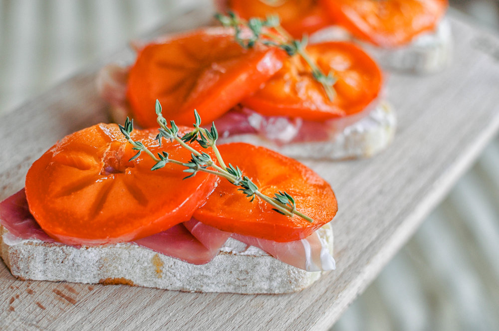 Persimmon Prosciutto Crostini - This simple recipe for persimmon prosciutto crostinis with homemade ricotta is a wonderful appetizer, snack, or light lunch.