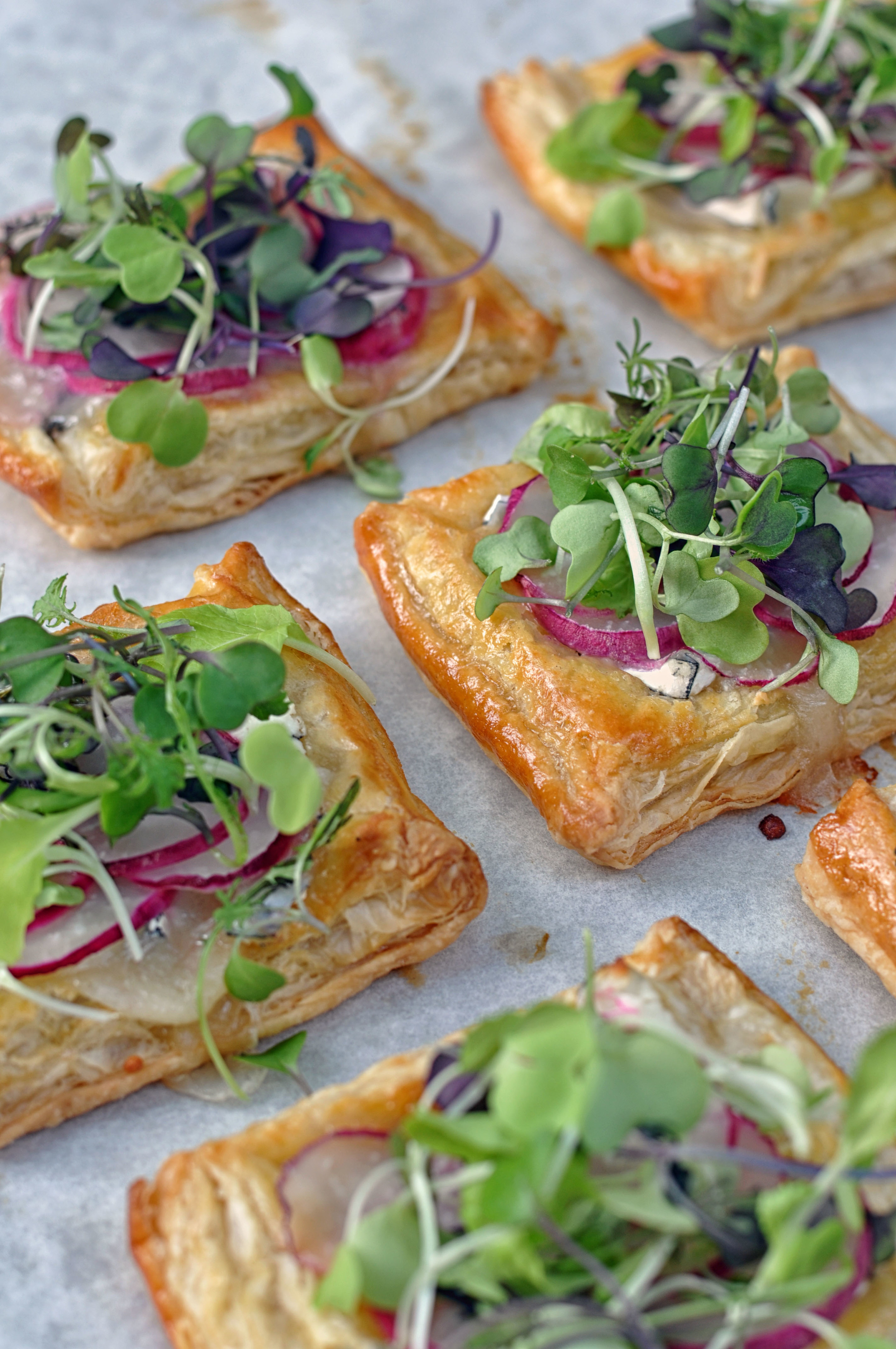 Mini Radish Puffs - These mini puff pastry tarts with goat's cheese, radishes, and microgreens are delicious, peppery, and delightfully rich. They are a perfect appetizer or cocktail party pass around.
