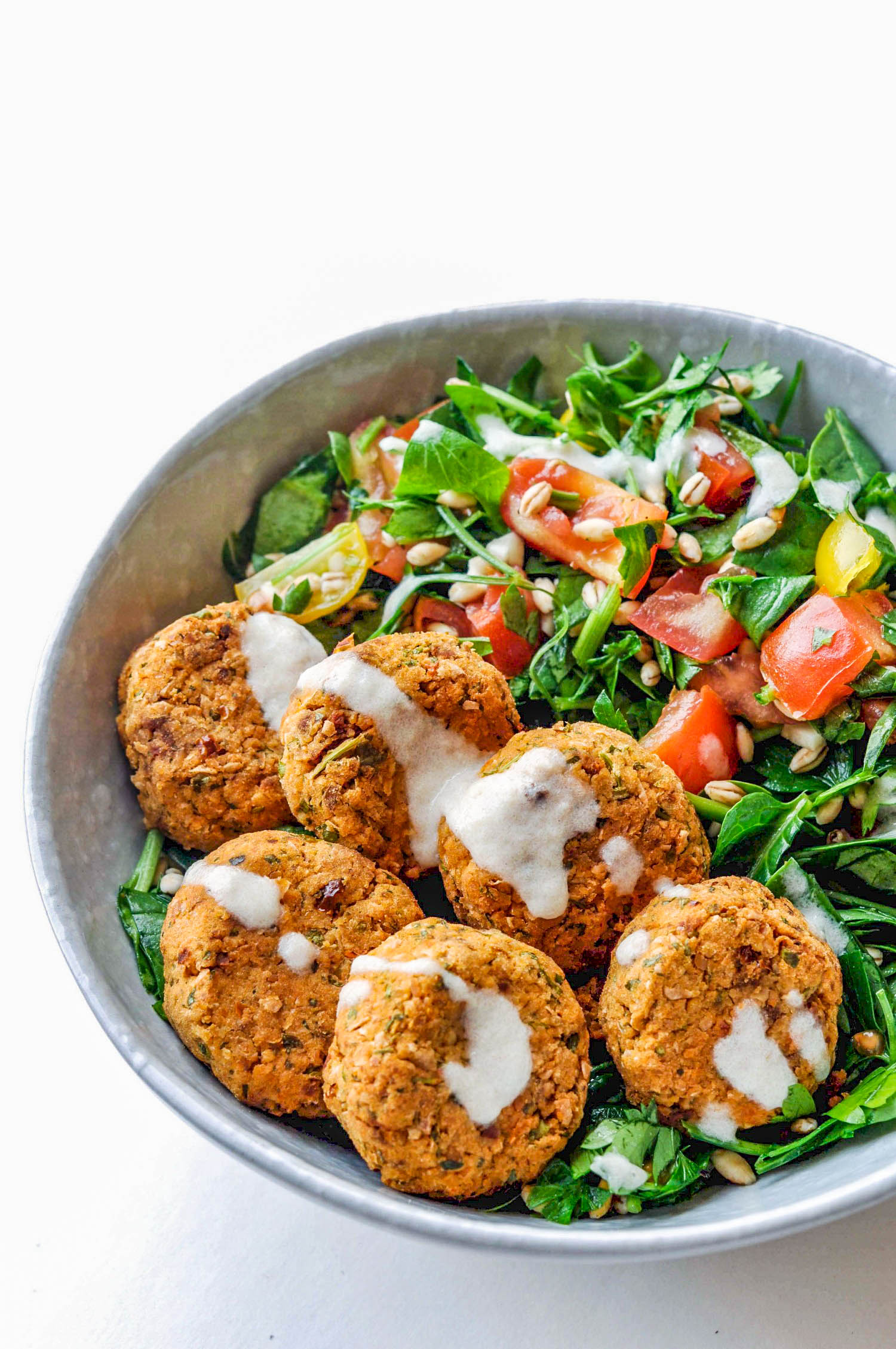 Baked sun-dried tomato falafels with a bulgur salad and tahini dressing. A healthy, vegan recipe.