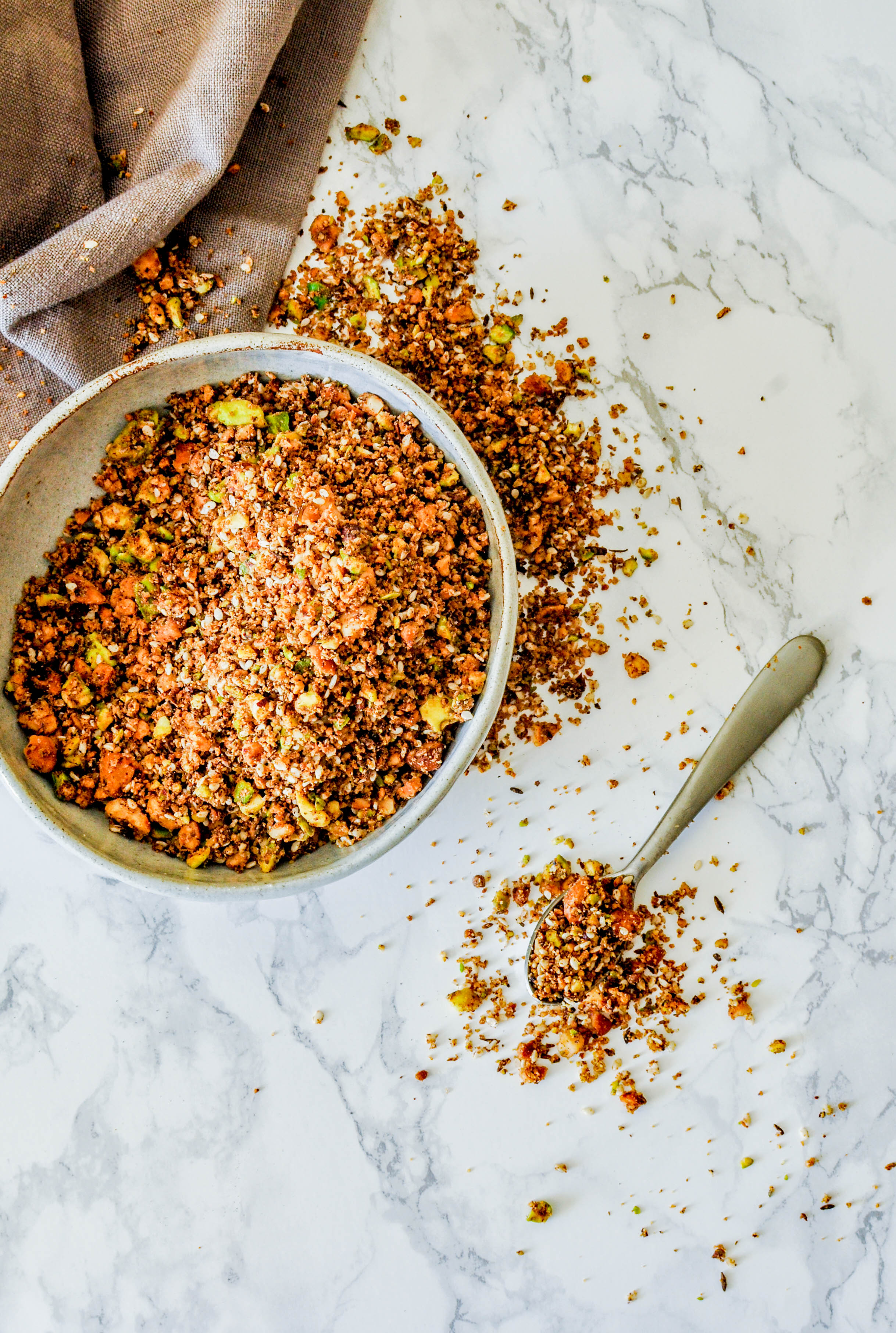 """Dukkah, in Arabic, means """"to crush"""" or """"to blend"""". In Egypt, dukkah is used as an all-purpose spice and often families and vendors have their own blends. Because the seeds, spices, and nuts are crushed the meld together to create an aromatic blend. The versatile blend can be used as a rub on fish or meat, sprinkled on salad, or stirred into a dip (hummus, yogurt, or muttabel) to add some complexity."""