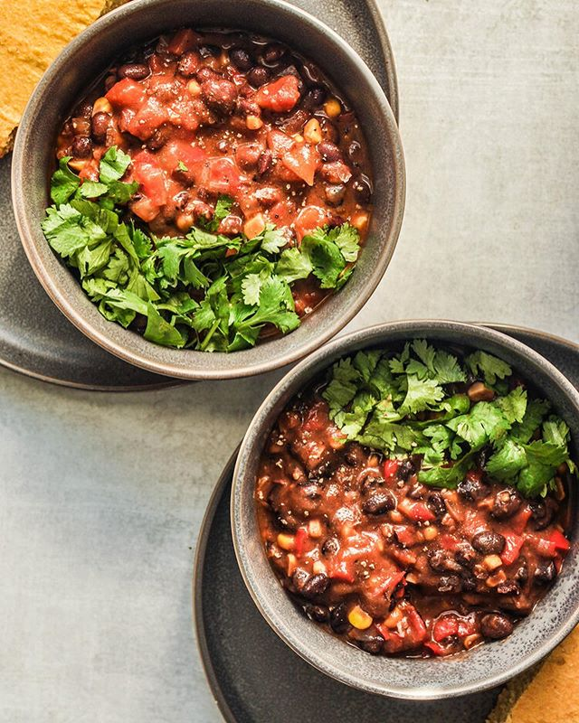 """This easy black bean chili recipe is vegan, gluten-free, and full of flavor! This hearty soup is made from simmered black beans, tomatoes, corn, bell peppers, onion, vegetable stock, and lots of spices.  It's one of my all-time favorite weeknight meal recipes, because it only requires 15 minutes of real hands-on time and the rest of the time it just simmers. .  To see the recipe, click the link in my profile and search my site for """"black bean chili"""". . . . . . #blackbeans #chili #soup #autumncooking #dinner #healthydinner #mindbodygram #thenewhealthy #glutenfree #healthyrecipe #cleaneats #food_glooby #jjusteatrealfood #bhgfood #balancedliving #foodphotography #food52 #inmykitchen #food4thought #buzzfeedfood #realsimple"""
