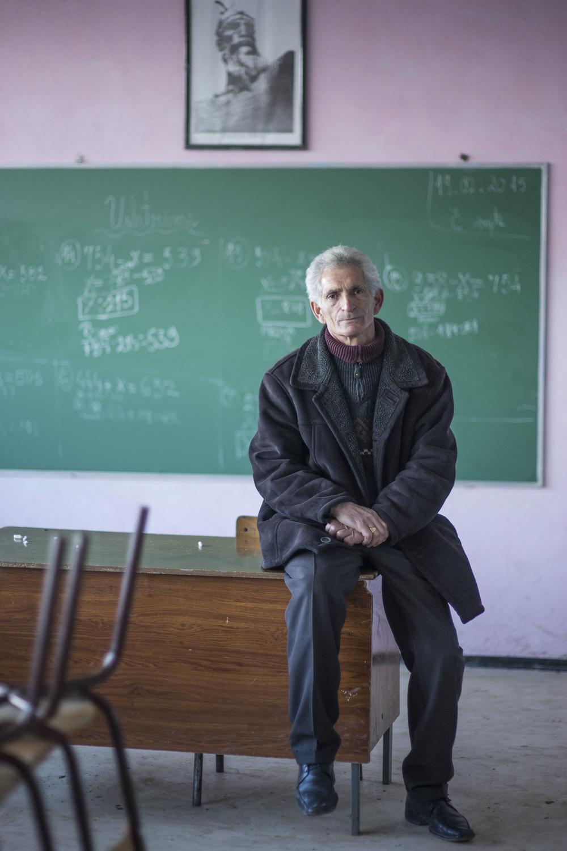 Teacher Enver I( 61) sitting in an empty classroom after school