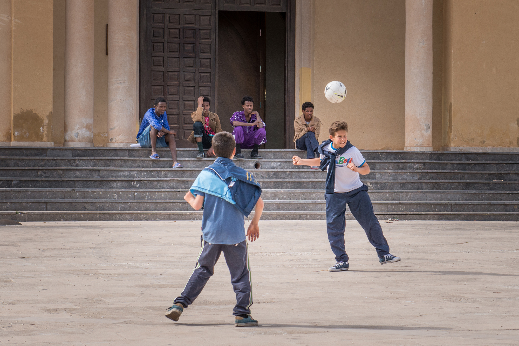 Young refugees sit on the church steps and watch a group of Italian kids playing football.
