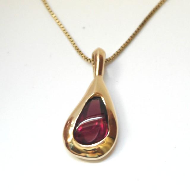 Gold teardrop pendant with tourmaline.