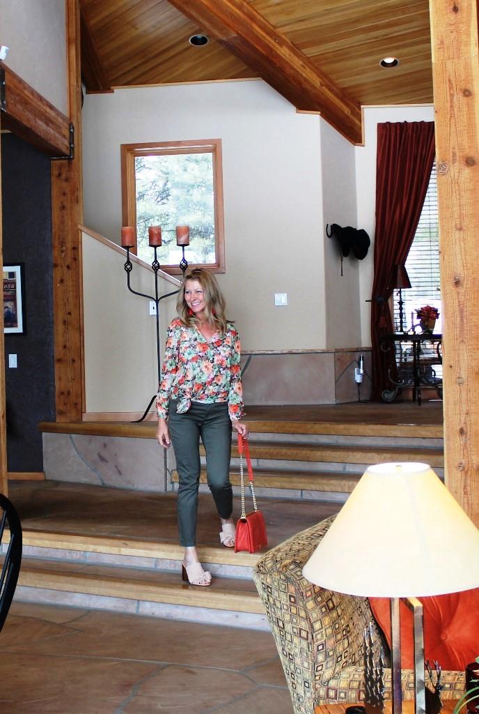 My look . . . - Sheer floral top, dark green pants, nude mules and an orange bag and tassel earrings.