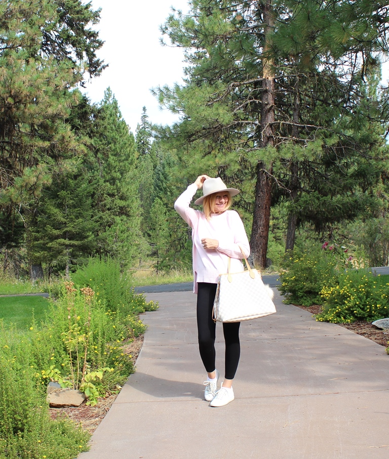 Look 2 - Here I am wearing a pale pink sweater, white sneakers and a tan hat. I am carrying my Louis Vuitton Never Full GM tote.