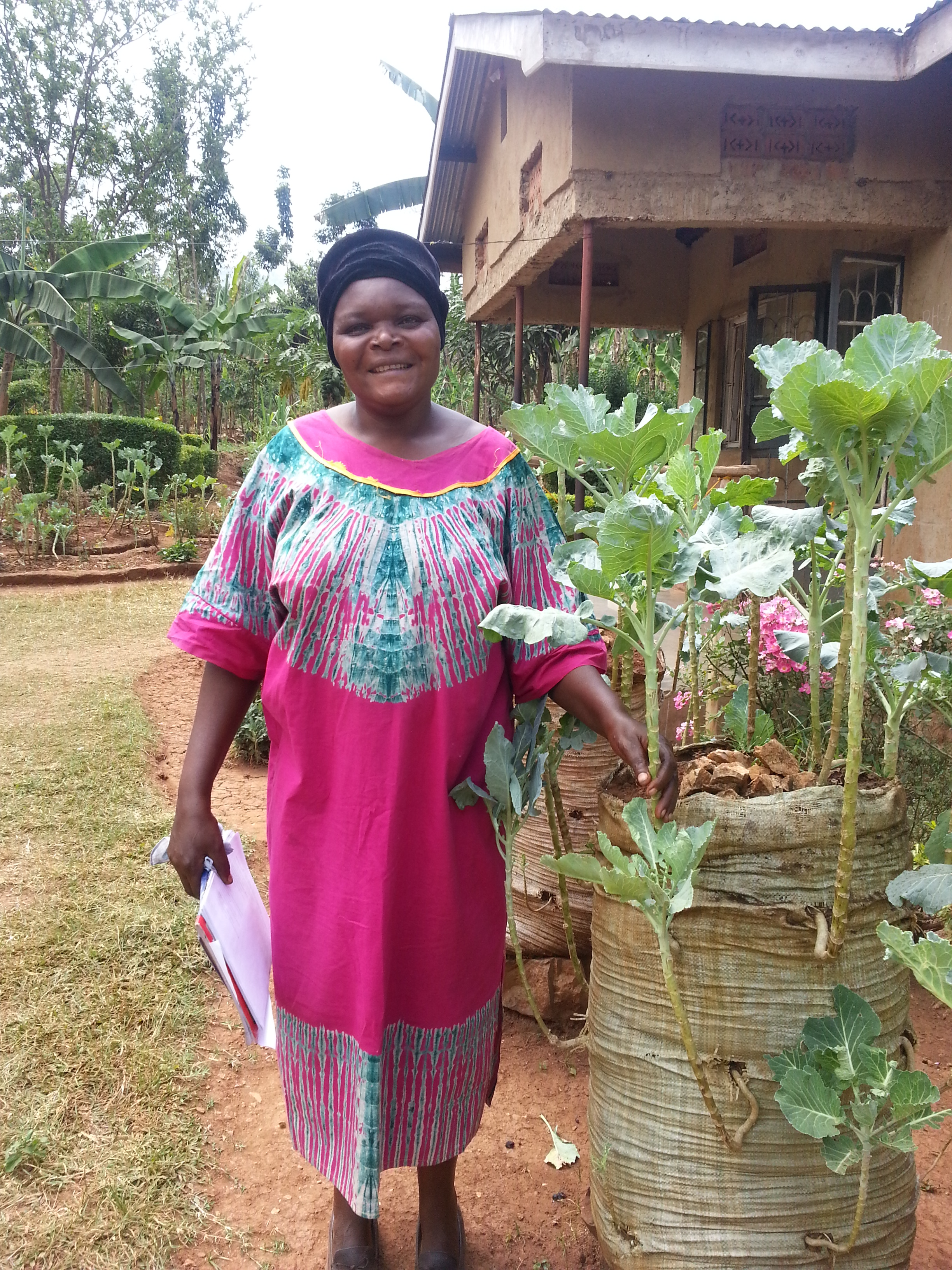 Pictured: Marguerite in Kenya with her water saving bag garden. Image credit: Send a Cow