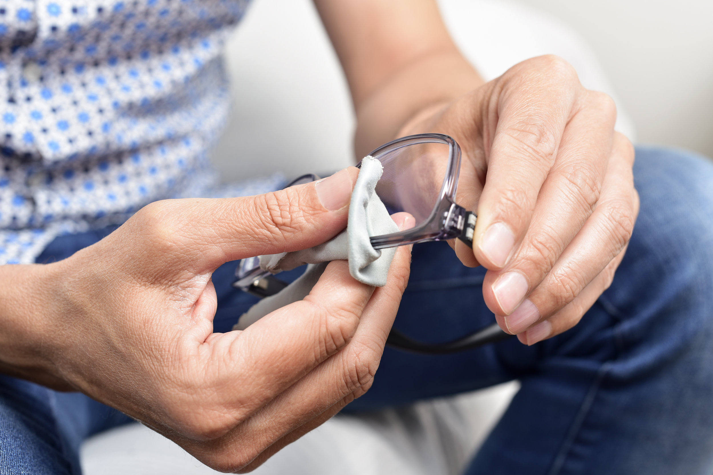 Man cleaning his eyeglasses with a cleaning cloth