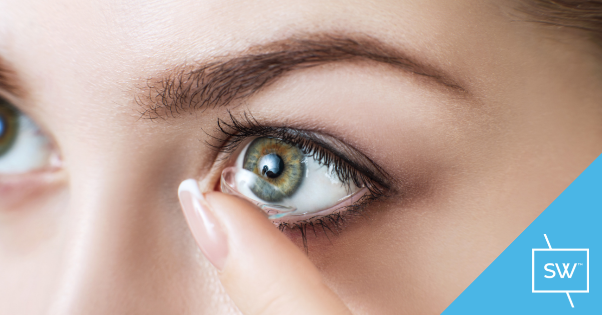 Young lady inserting a 1-day disposable contact lens onto a blue green eye