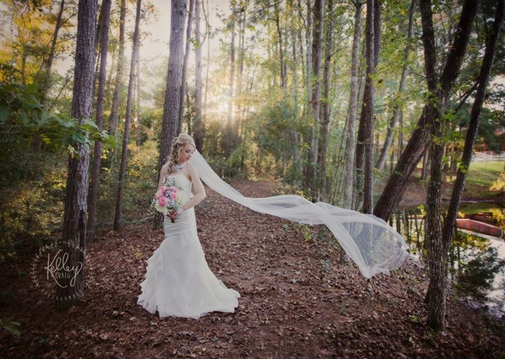 A beautiful bride posing on the pathway located on the far side of the pond.