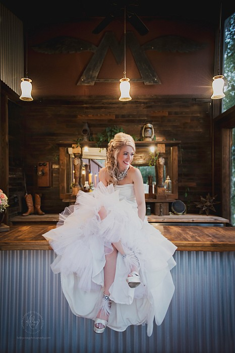 Another beautiful bride posing on the bar top in the Flying M Bar during her Bridal Shoot.
