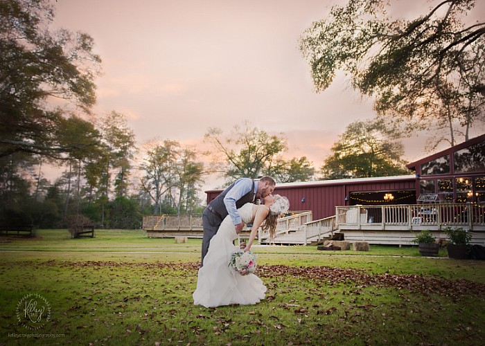 A beautiful couple enjoys a kissing front of the pond with the event area in the background.