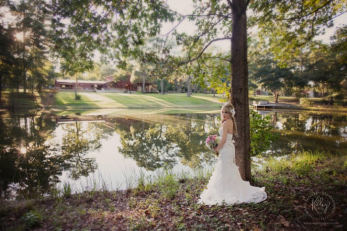 A gorgeous bride posing on the far side of the pond with the event area in the background.