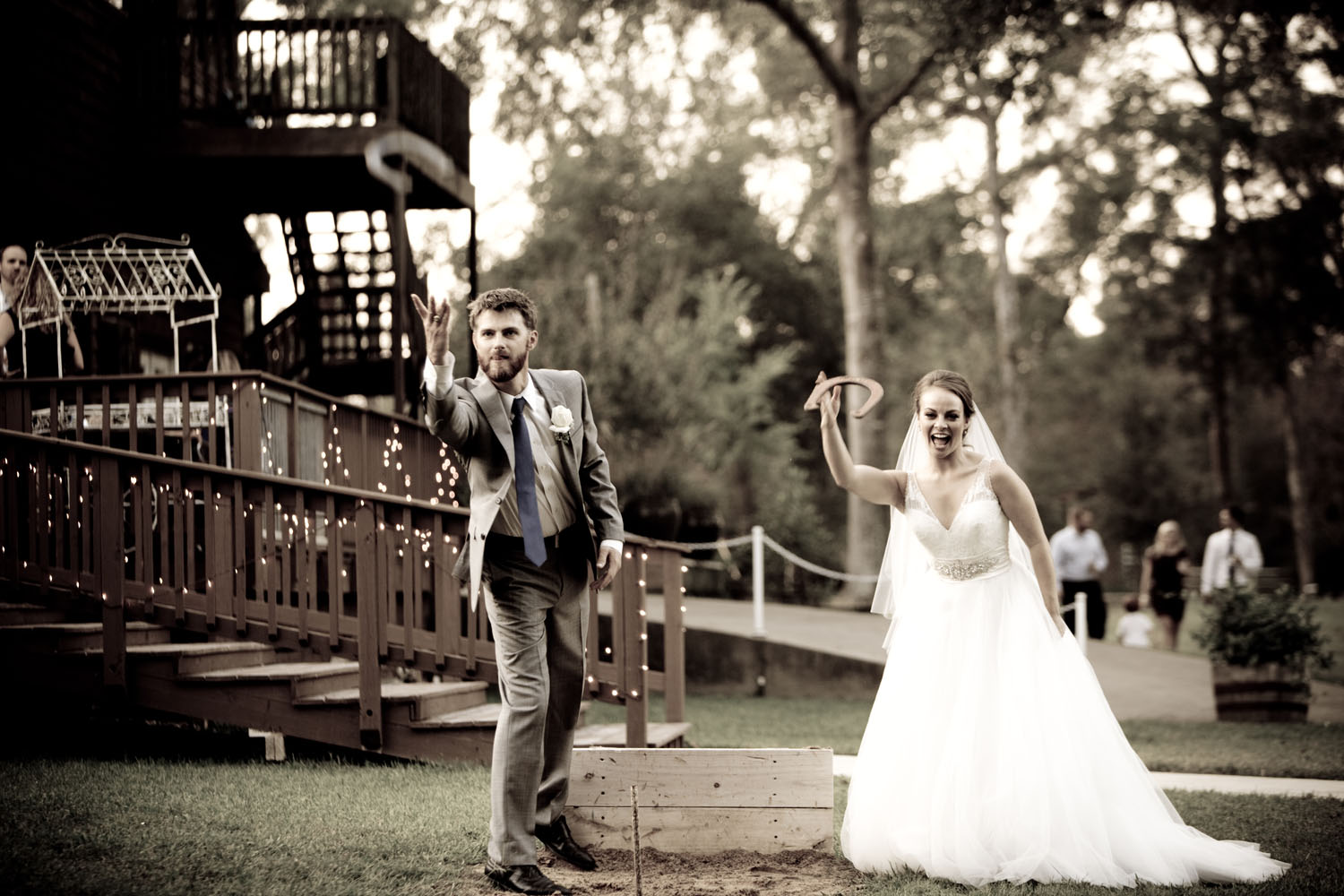 A bride and groom having a friendly game of horseshoes just off the deck.