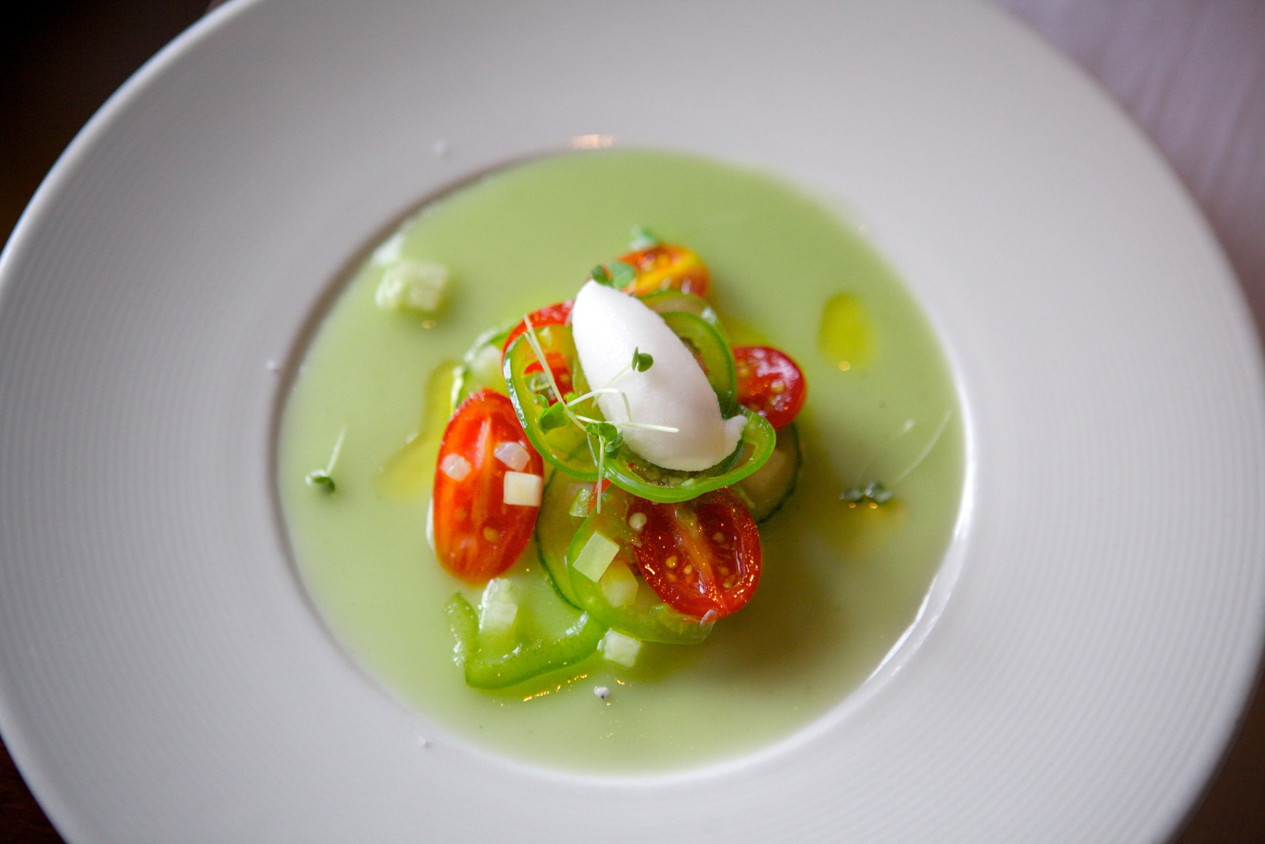 Above:  a chilled cucumber soup topped with grape tomatoes, sliced jalapeños, pickled watermelon rind, and jalapeño sorbet.