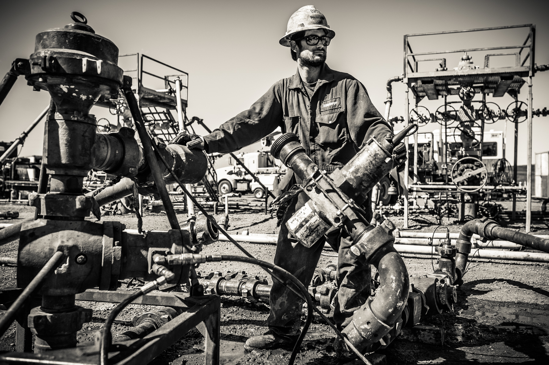 "A worker at a frack site, aka a ""fracker,"" installing part of the massive plumbing project that will lead to the fracking of this oil well."