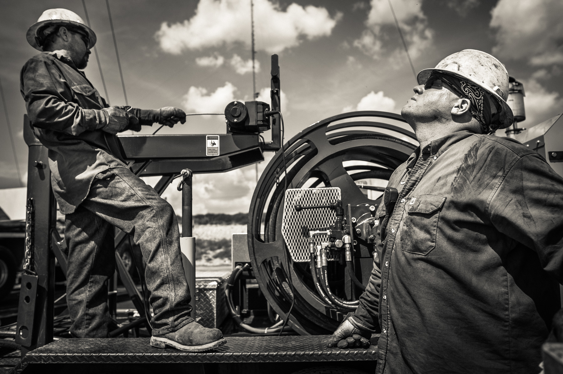 Men from a workover crew lifting a swivel head into place to complete the fracking of an oil well. Crews work in alternating 12 hour shifts throughout the entire drilling and fracking process. The work never stops on a drill site.