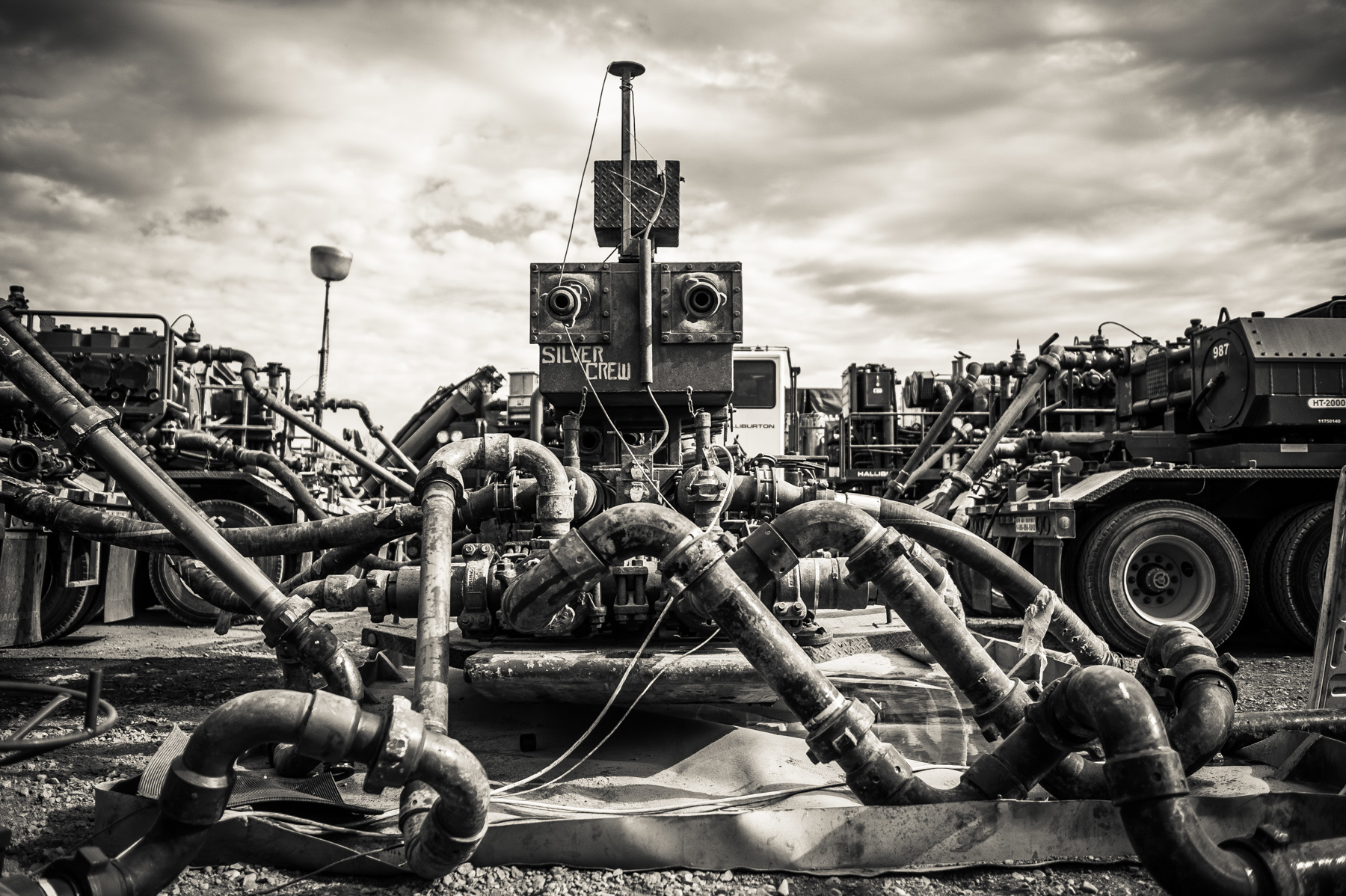 An oil well head during the process of Hydraulic Fracturing, aka fracking. The many pipes leading into the well contain water, sand and some chemical lubricants forced in by the massive pump trucks in the background.
