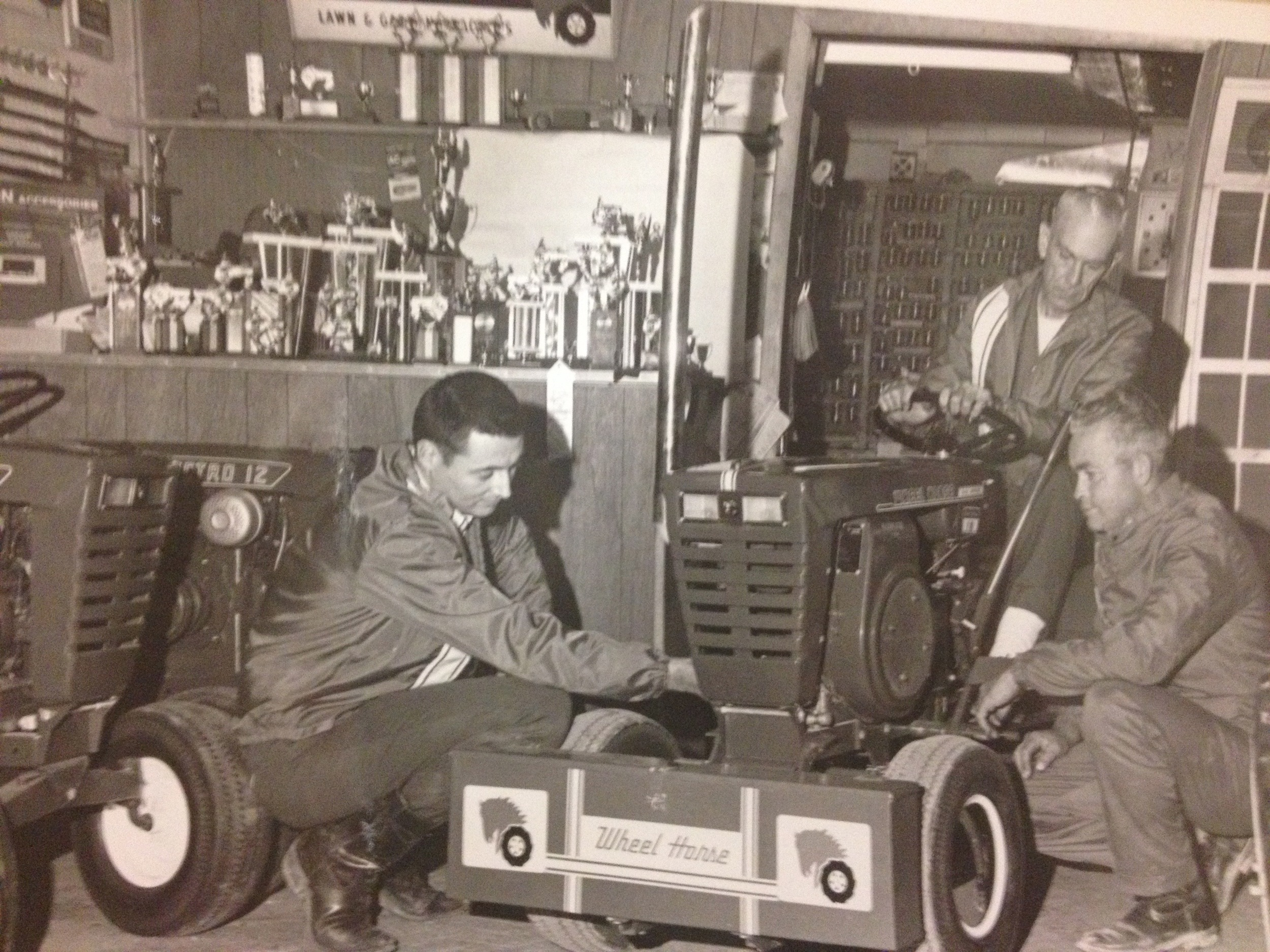 Phil Humphreys, Woody Porter (seated) and George York working in the Humphreys' Wheel Horse show room on Phil's hobby at the time, Garden Tractor pulling.