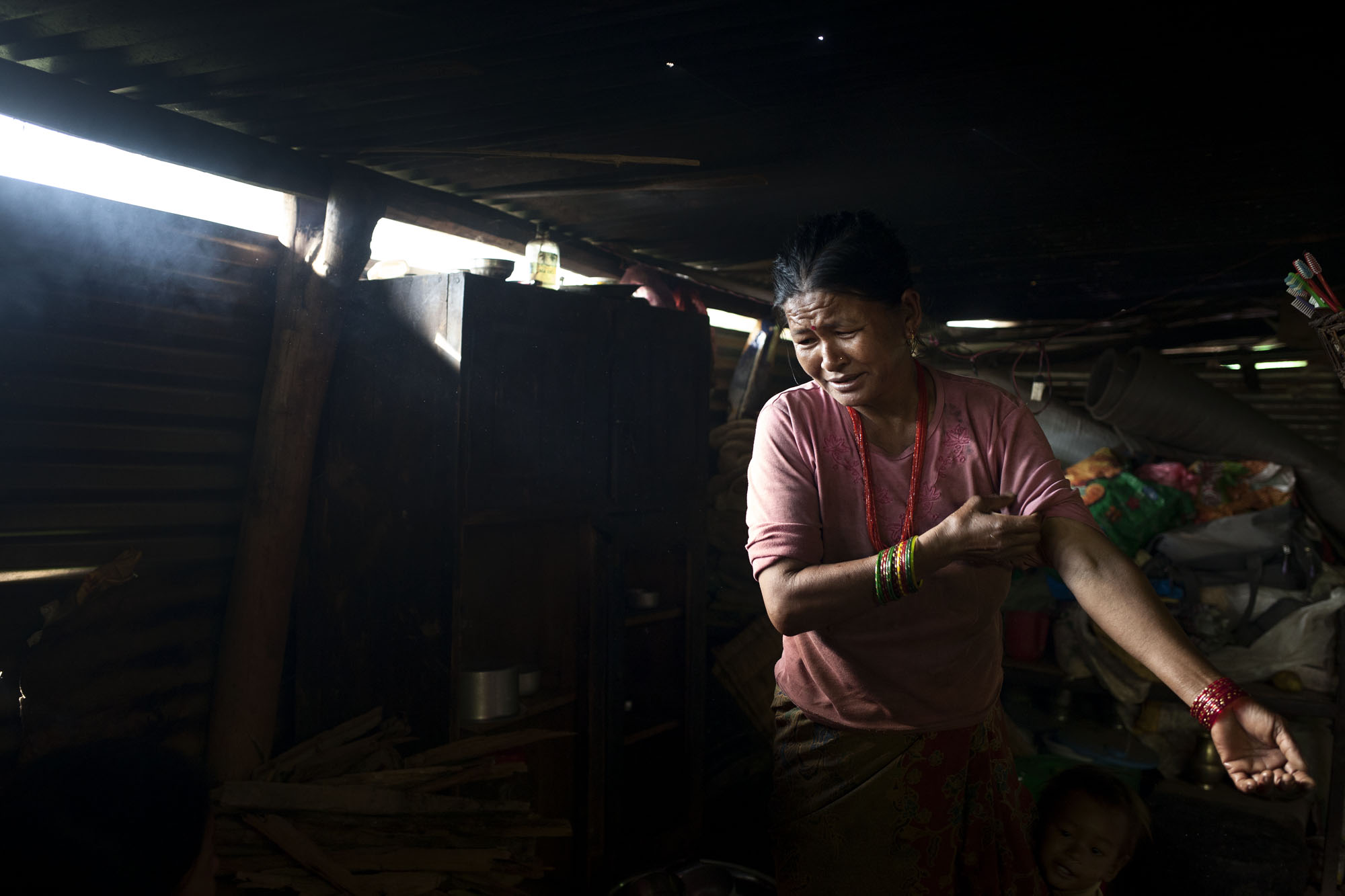 Hima Devp Magar age 46 prepares to make breakfast in her temporary shelter. Kandambas Village Ward No. 5 Sindupalcowk District, Nepal. July 30, 2015.