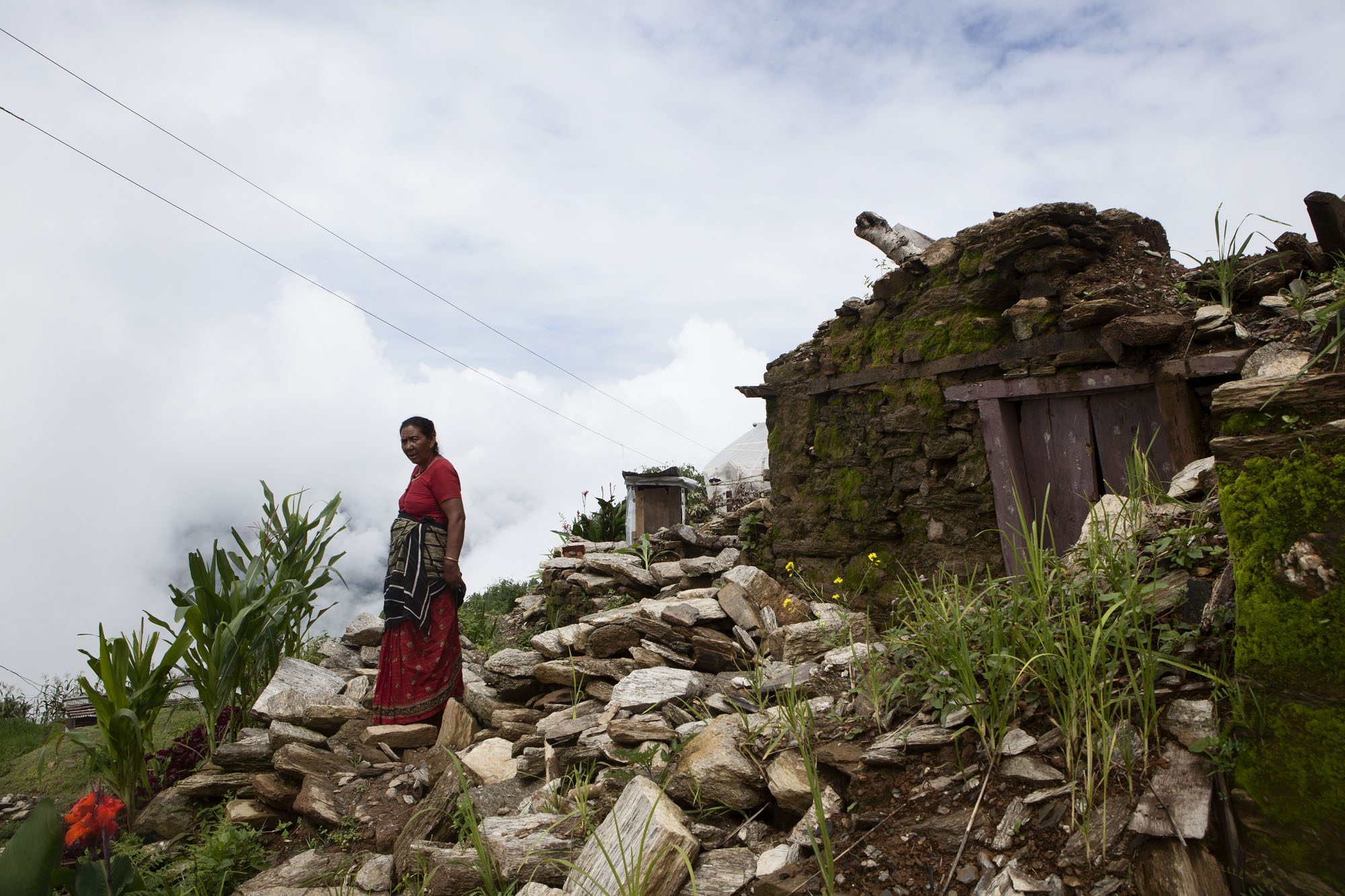 A Villager stands amongst rubble. Tauthali Village, Sindupalchowk District, Nepal. August 5, 2015.