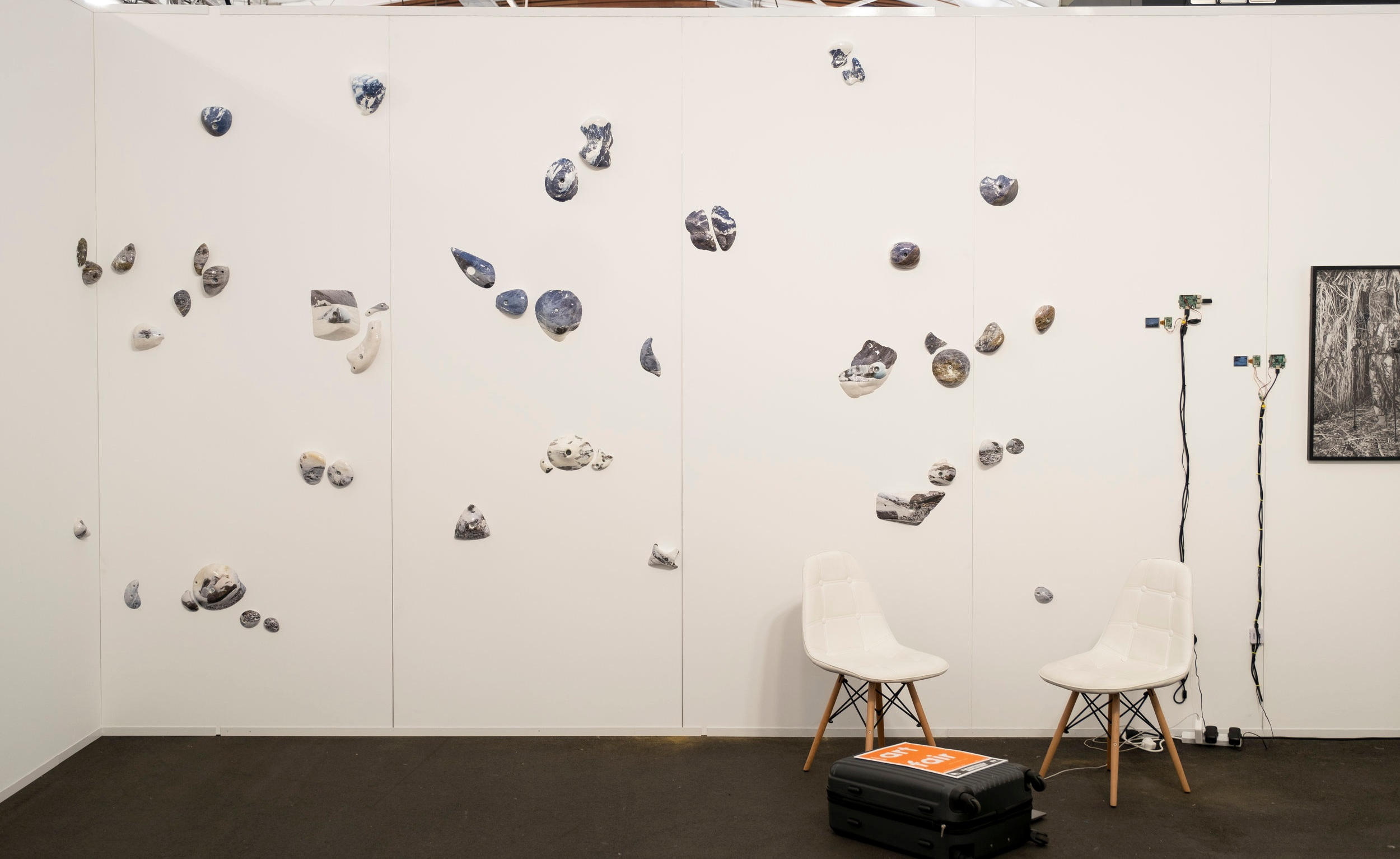Installation view Michael Bugelli Gallery, Auckland Art Fair. Kai Wasikowski artworks Left-Right:  Climb, grip, hold #3 , 2019, hydrographic prints on rock climbing holds, dimensions variable.  Streaming #4 , 2017, single channel video (5m 18s loop), LCD display, RaspberryPi, HDMI and component cables, 9 x 4 cm display, dimensions variable.  10 January 2017 #3 , 2017, single channel video (4m 29s loop), LCD display, RaspberryPi, HDMI and component cables, 7 x 3 cm display, dimensions variable.  Garden #2 , 2019, inkjet print on cotton rag, 77 x 60 cm. Image: Josef Scott.