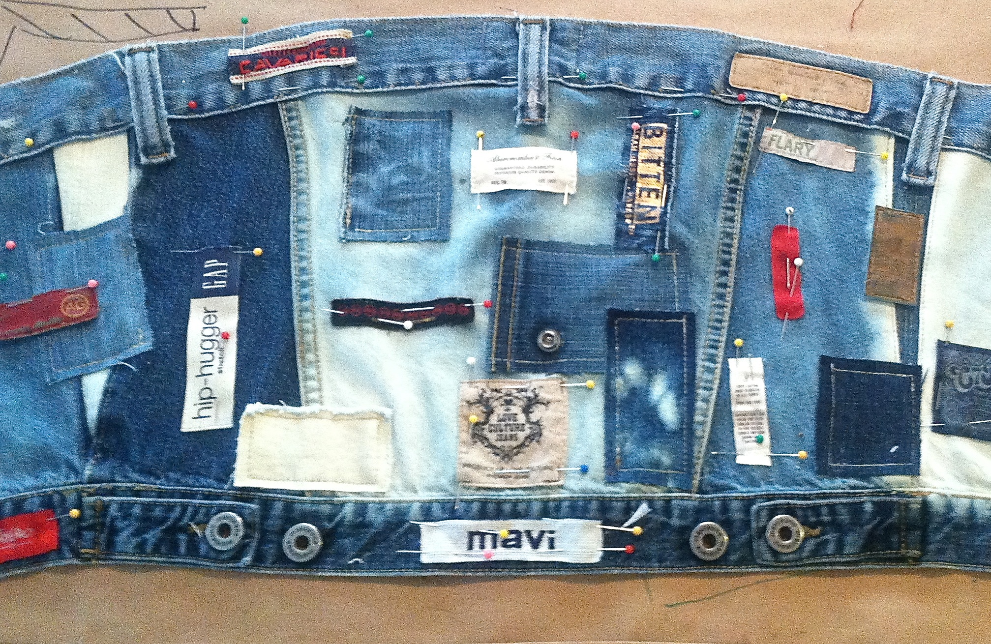 This started out as the back of a jean jacket, and I altered the shape, bleached sections, but left the bottom band intact.  The top band is a waistband from a pair of jeans, and I used the beltloops also.  As I ripped apart jeans for the skirt section, I fell in love with all the labels, so decided to sew them all over the bustier.
