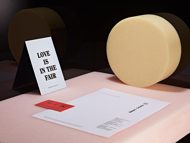 Aufsicht aug weisse Postkarte mit einem Holzstempel, der ein rotes Logo druckt und einer Pflanze auf Marmor.
