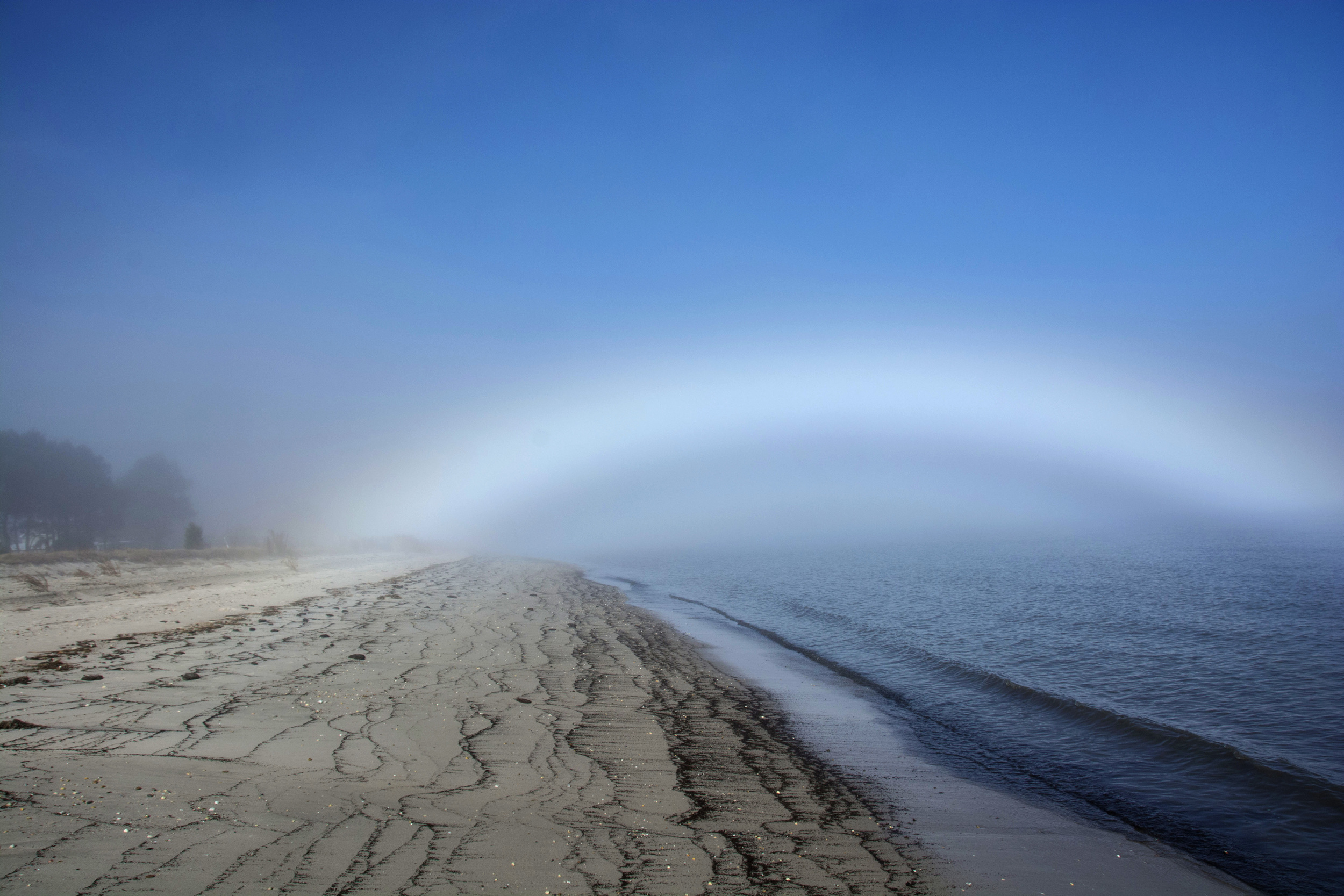 low rainbow as fog clears at Kitts Hummock Beach