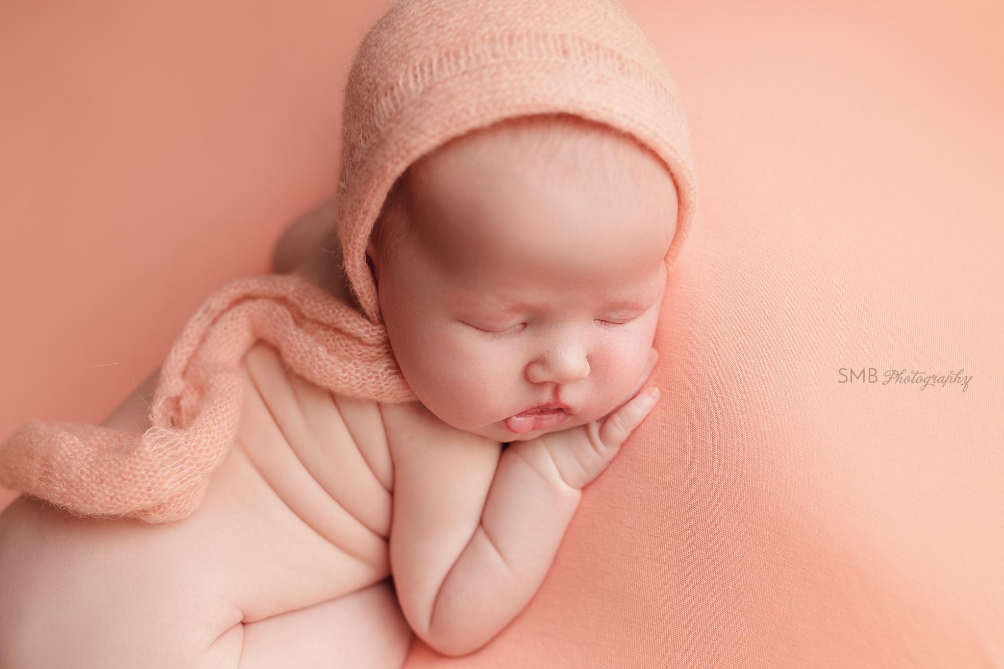 Newborn girl on peach blanket