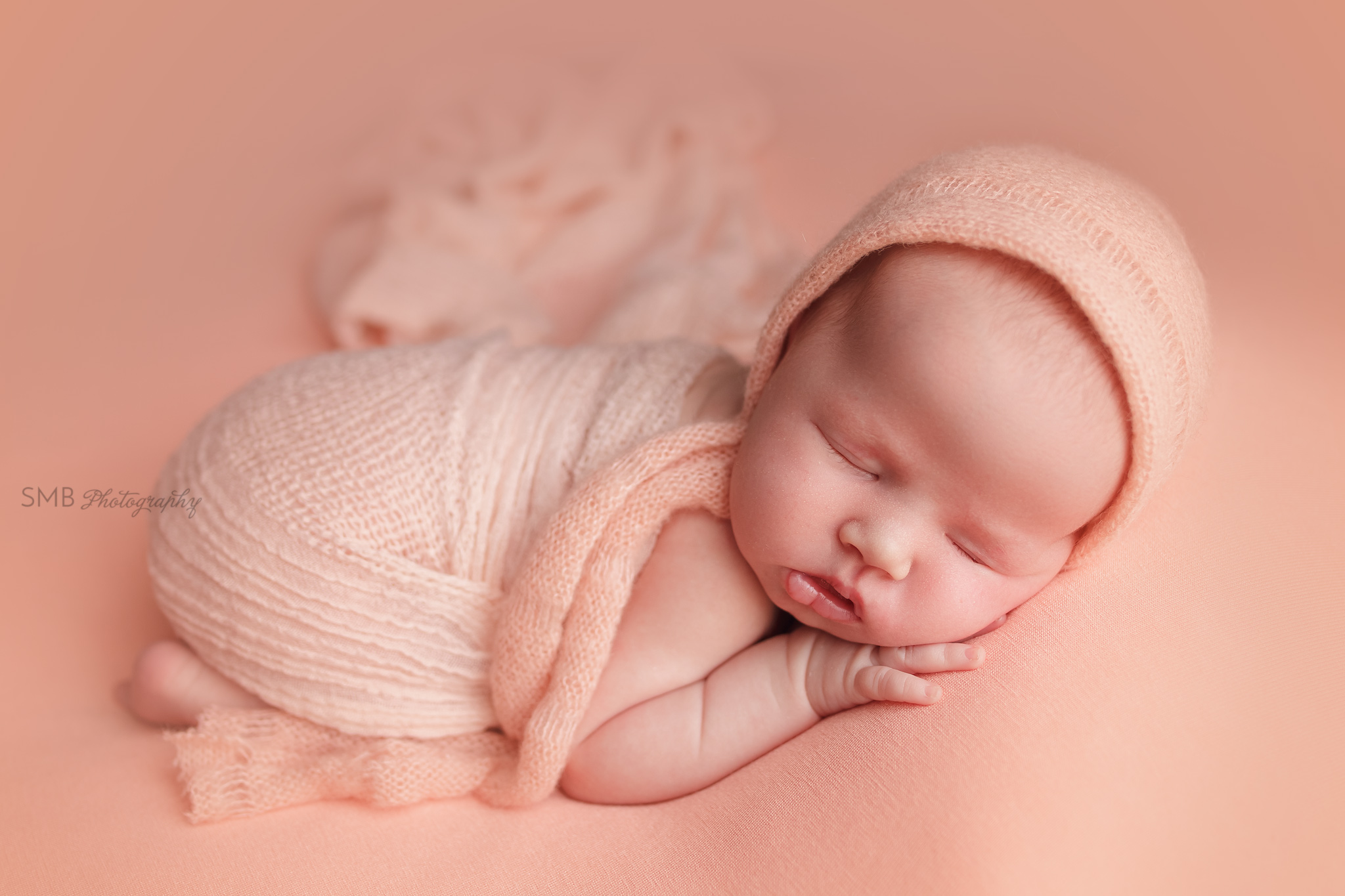 Newborn girl wrapped on peach blanket