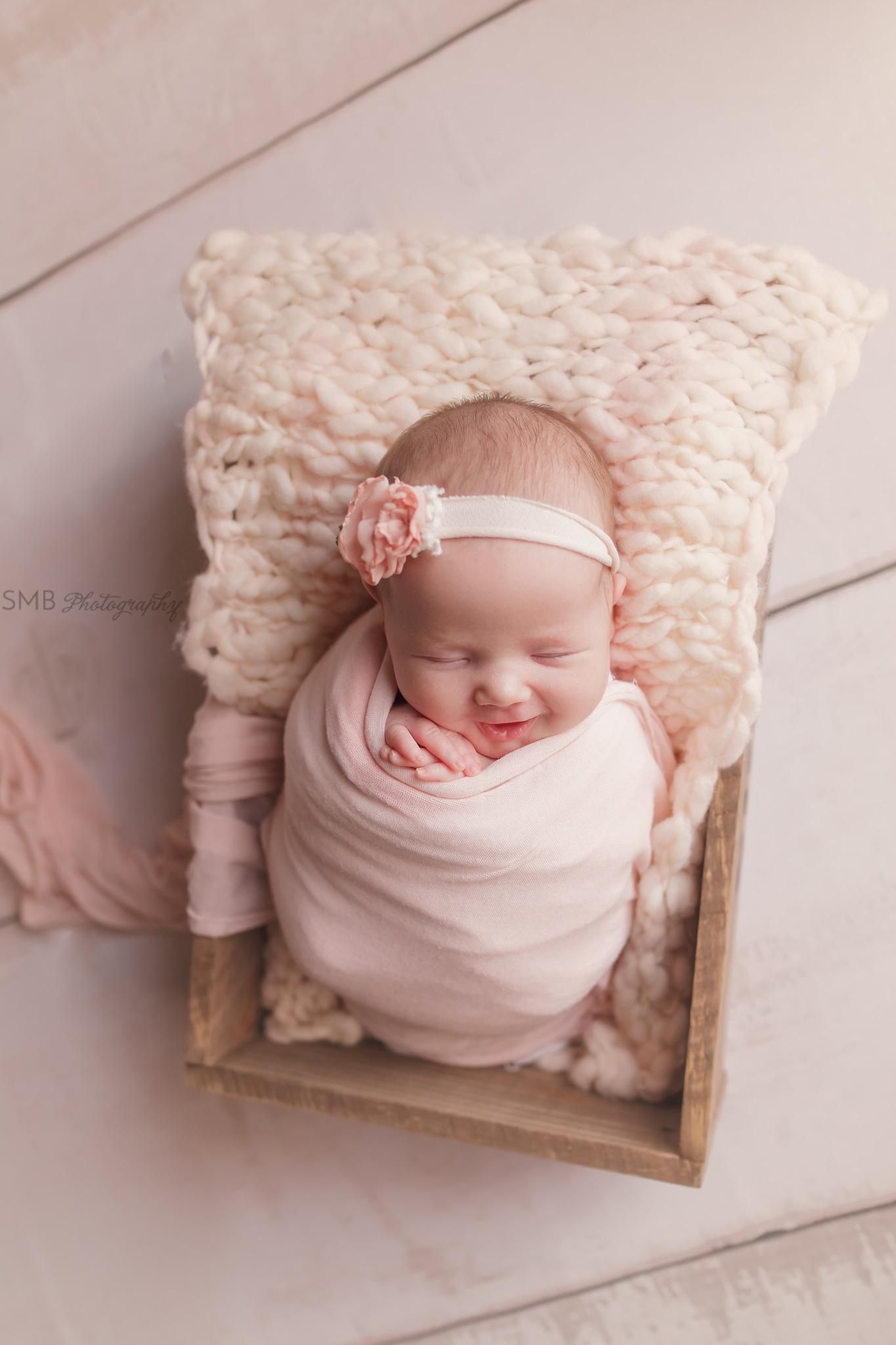 Newborn girl in wood box wearing pink