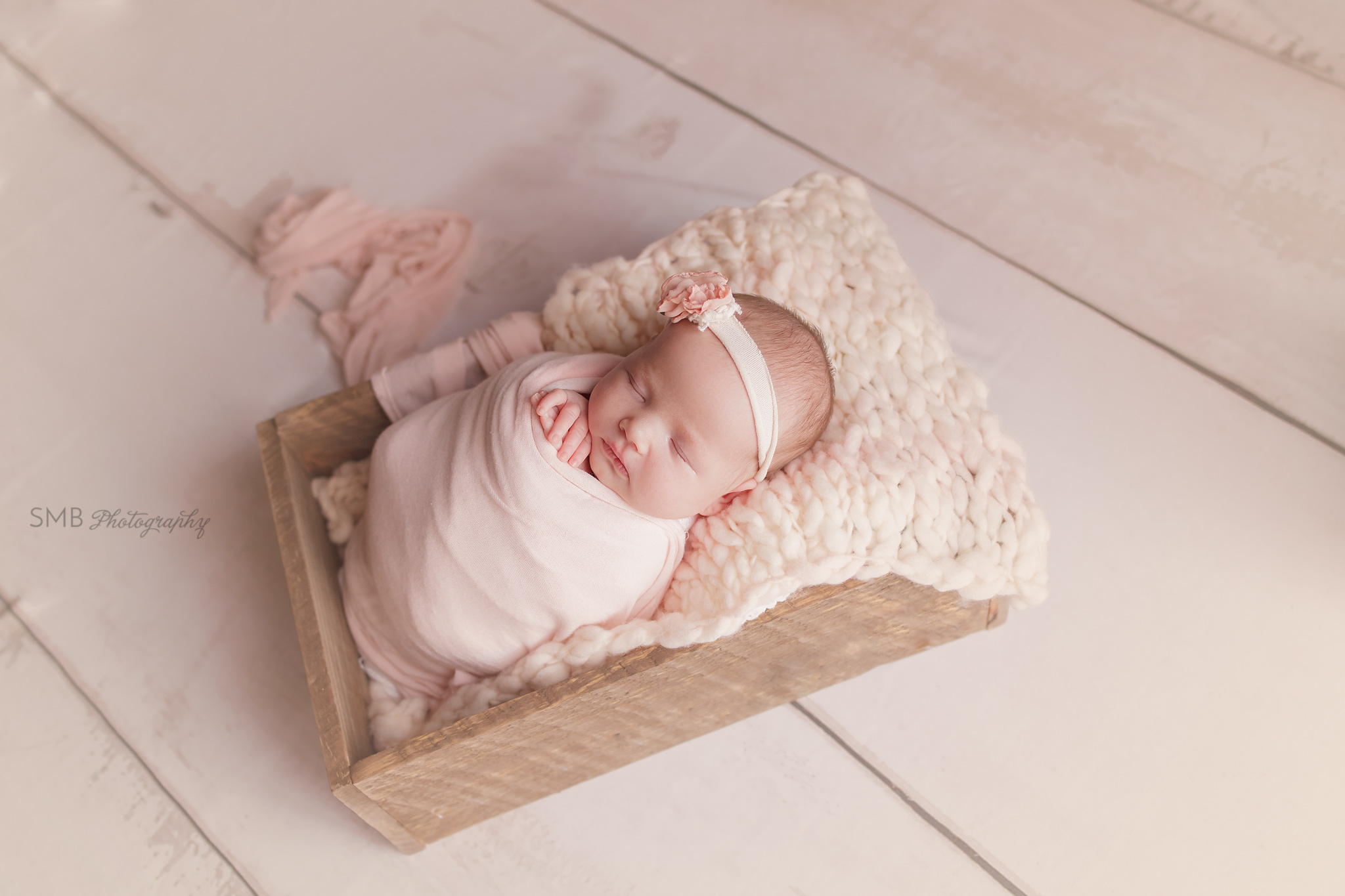 Newborn girl wrapped in pink on cream wood floor