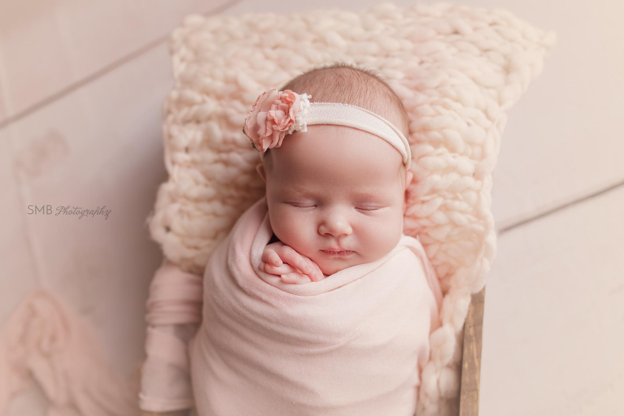 Newborn girl in wood box closeup of face