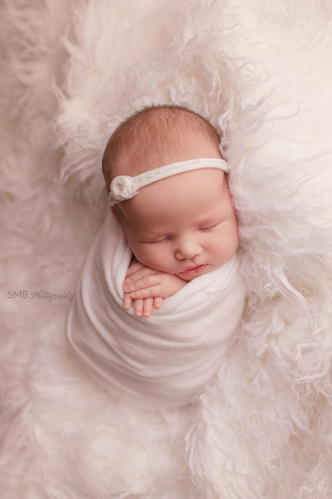 Newborn girl wrapped on white flokati