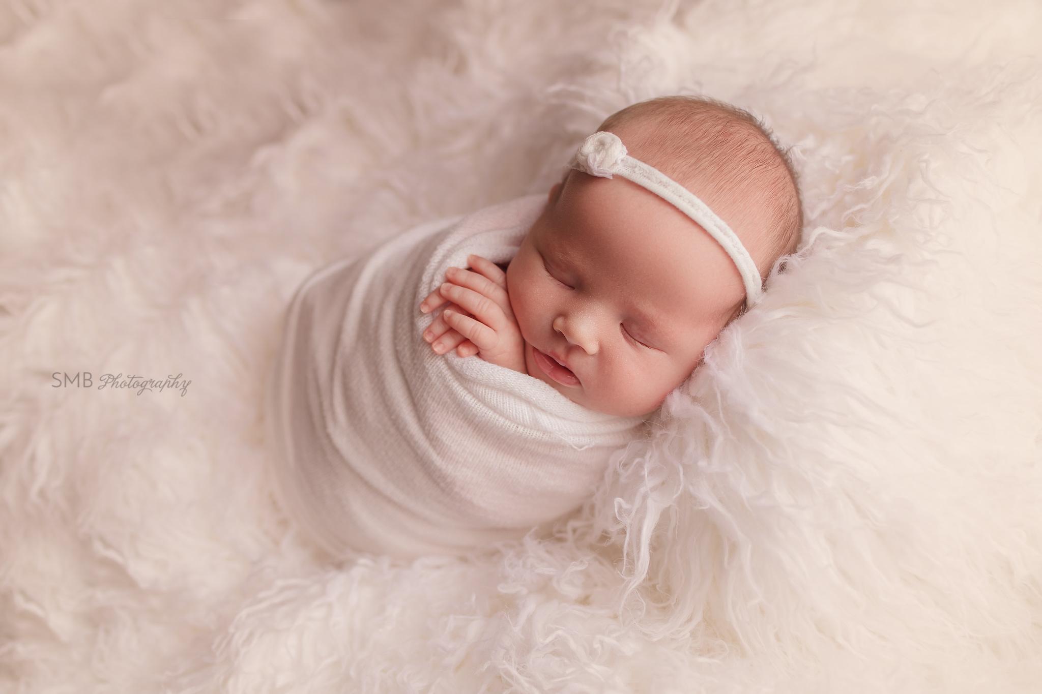 Newborn girl wearing white headband on white flokati