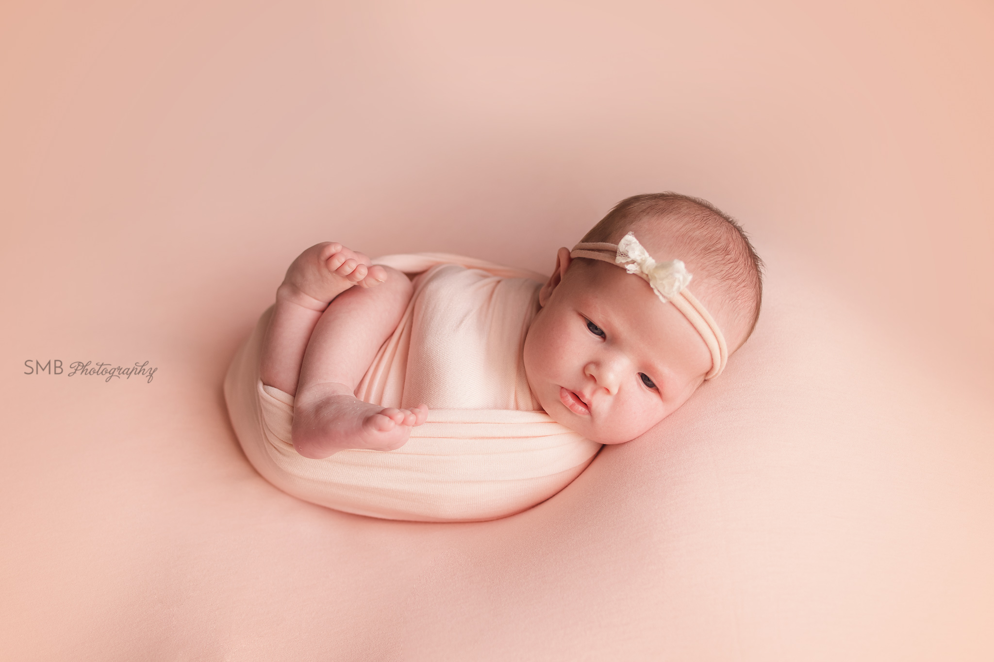 Newborn girl wrapped on pale peach blanket with eyes open