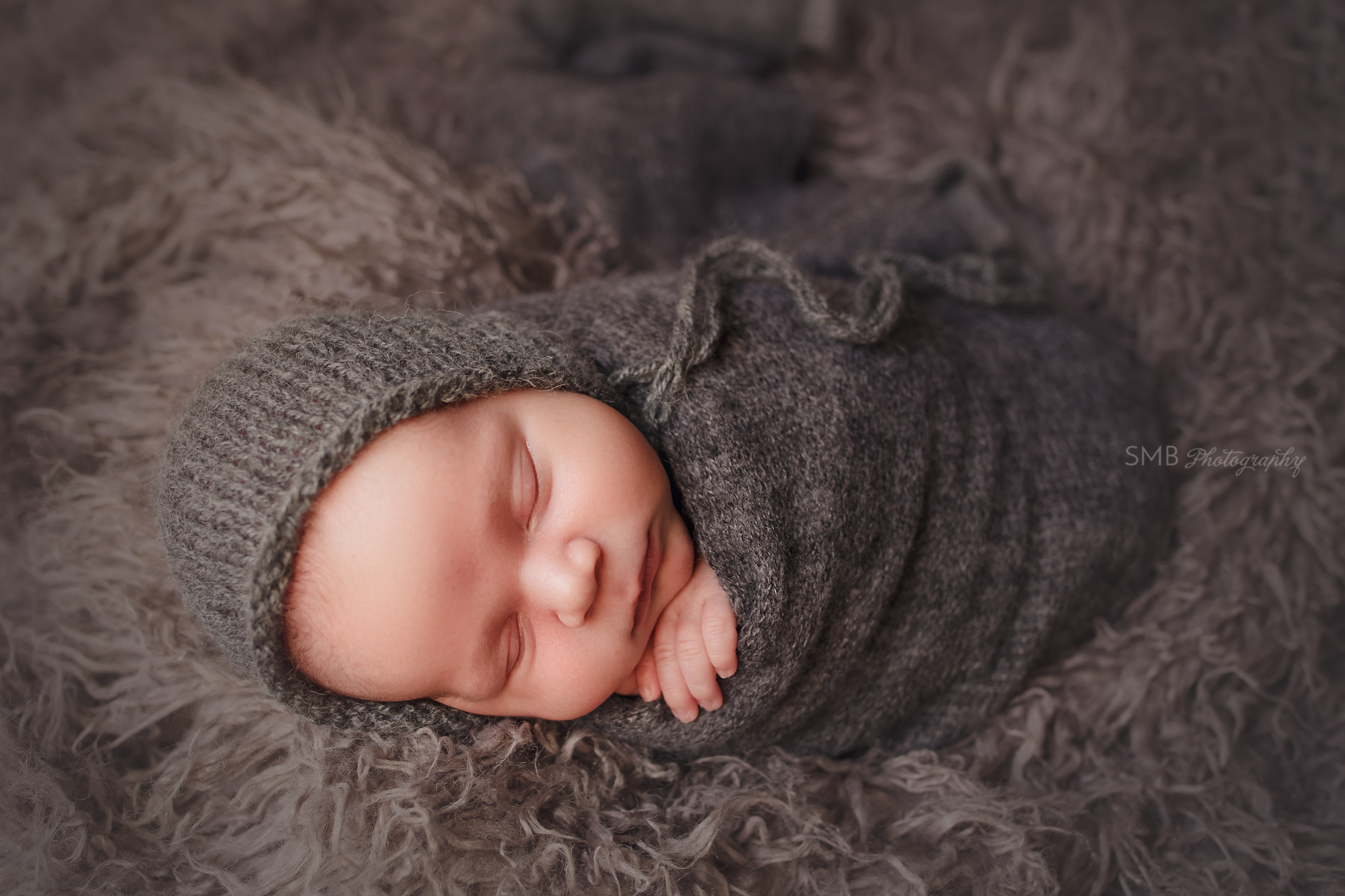 Newborn boy on gray flokati